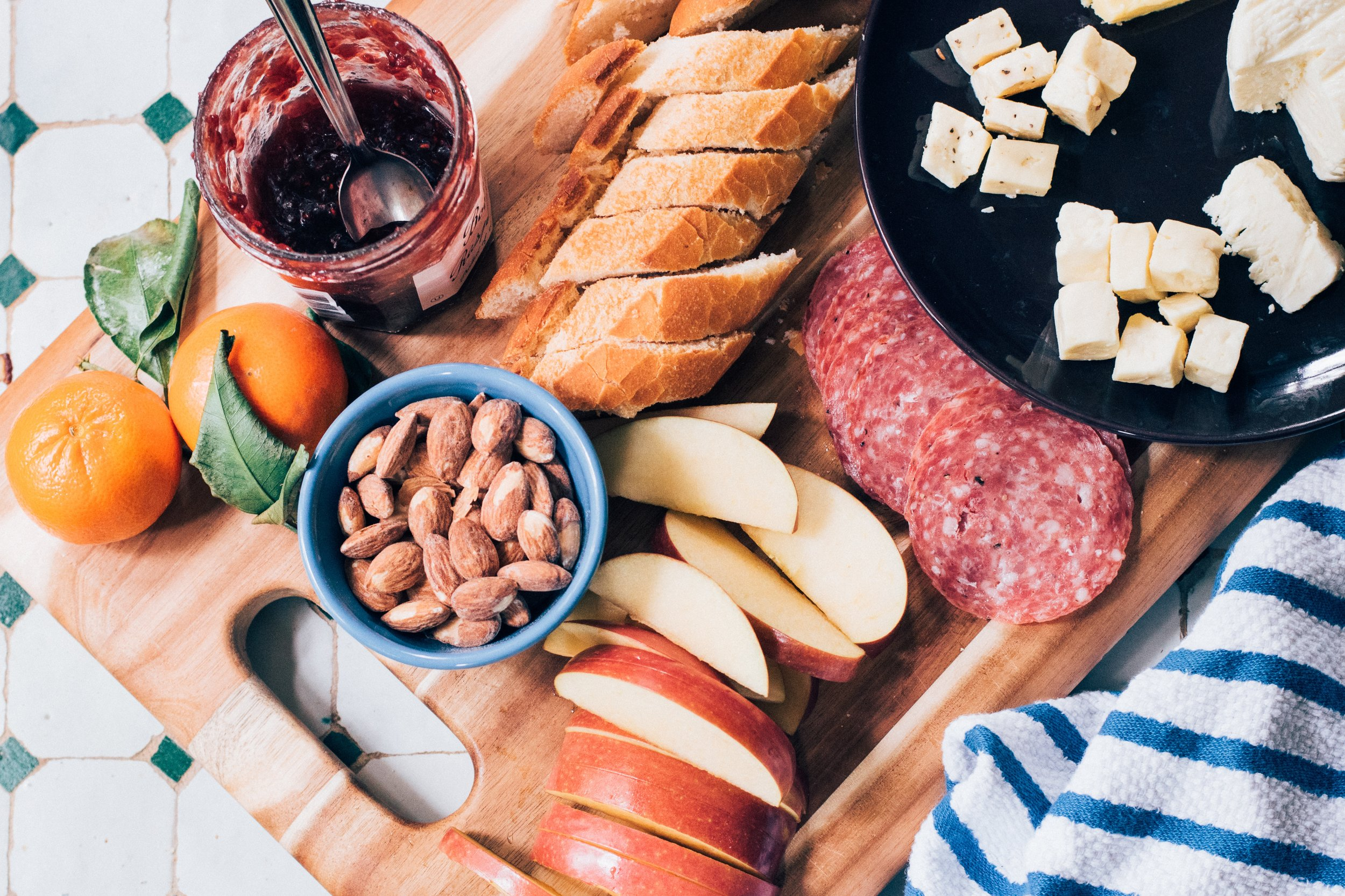 Your average snack board. A handful of almonds is 162 calories, 1 apple is 80 calories, 6 pepperoni slices is 100 calories, 1 baguette is 552 calories, an entire wedge of brie cheese is 522 calories, a spoon of jam is 26 calories, an orange is 64 calories. *This is a rough estimate thanks to Google and Tesco Online's product nutritional information