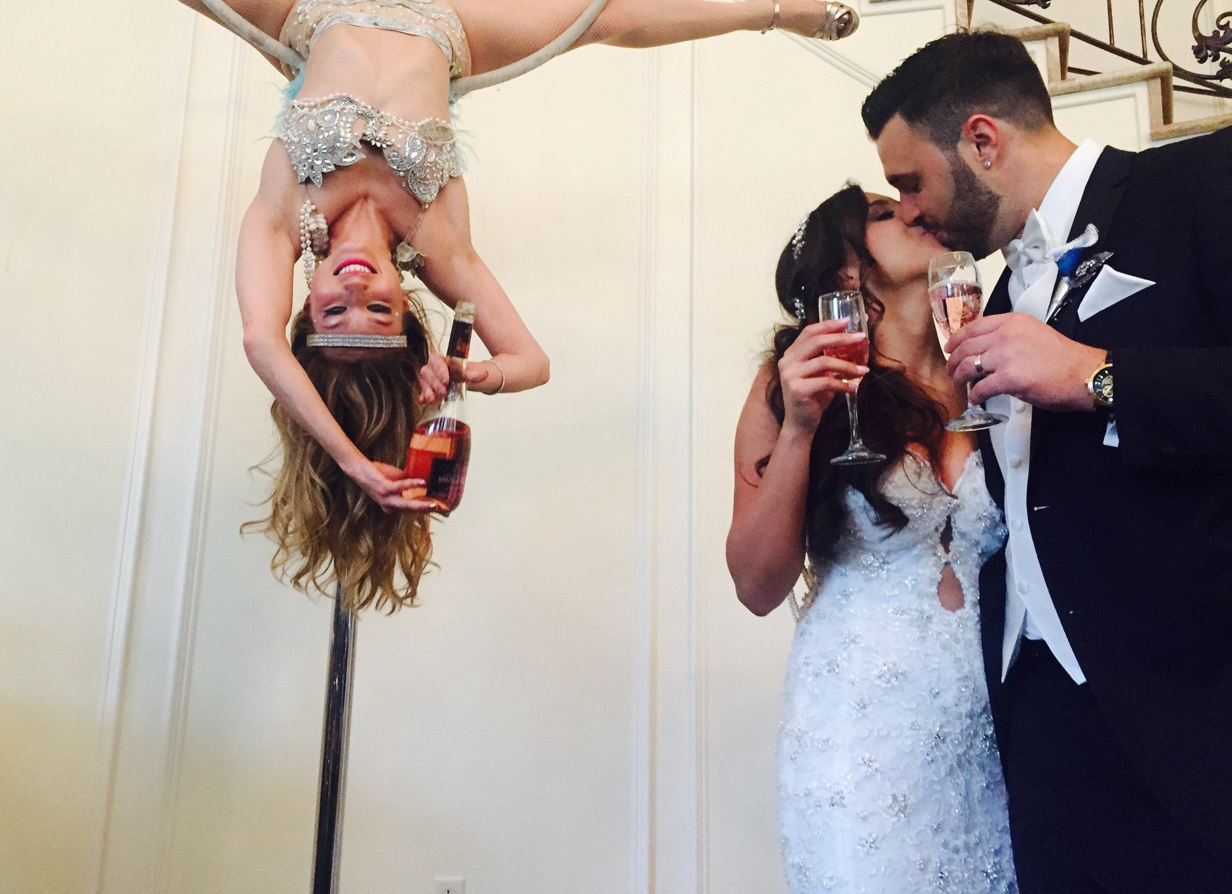 Bride and Groom toast with a kiss right after being served by a beautiful girl hanging upside down and pouring rose!