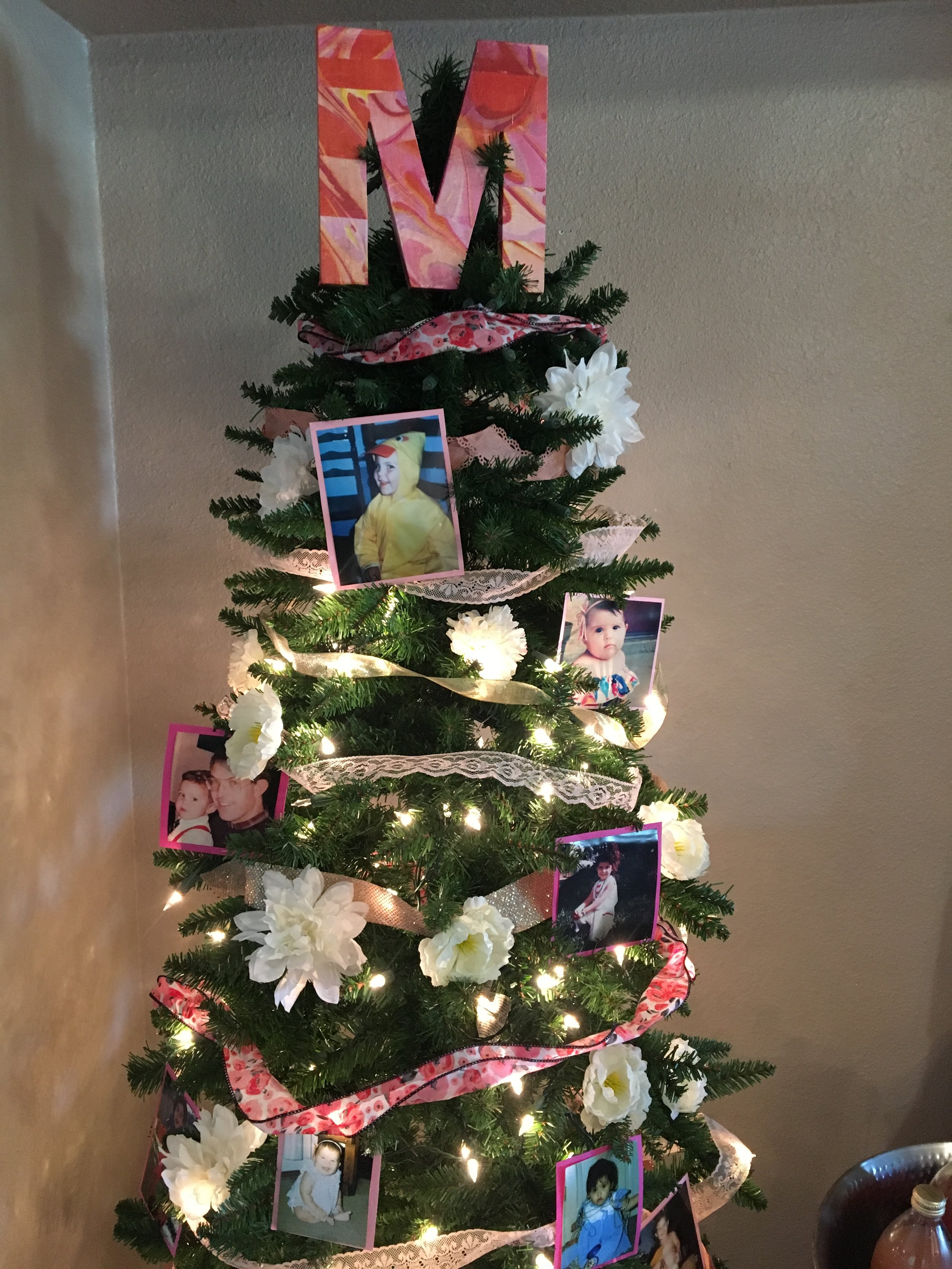 Meredith keeps up a year-round tree, with different themes. How cute is this? Our baby pictures served as decorations. The topper is also now part of Baby Marisa's nursery decor.