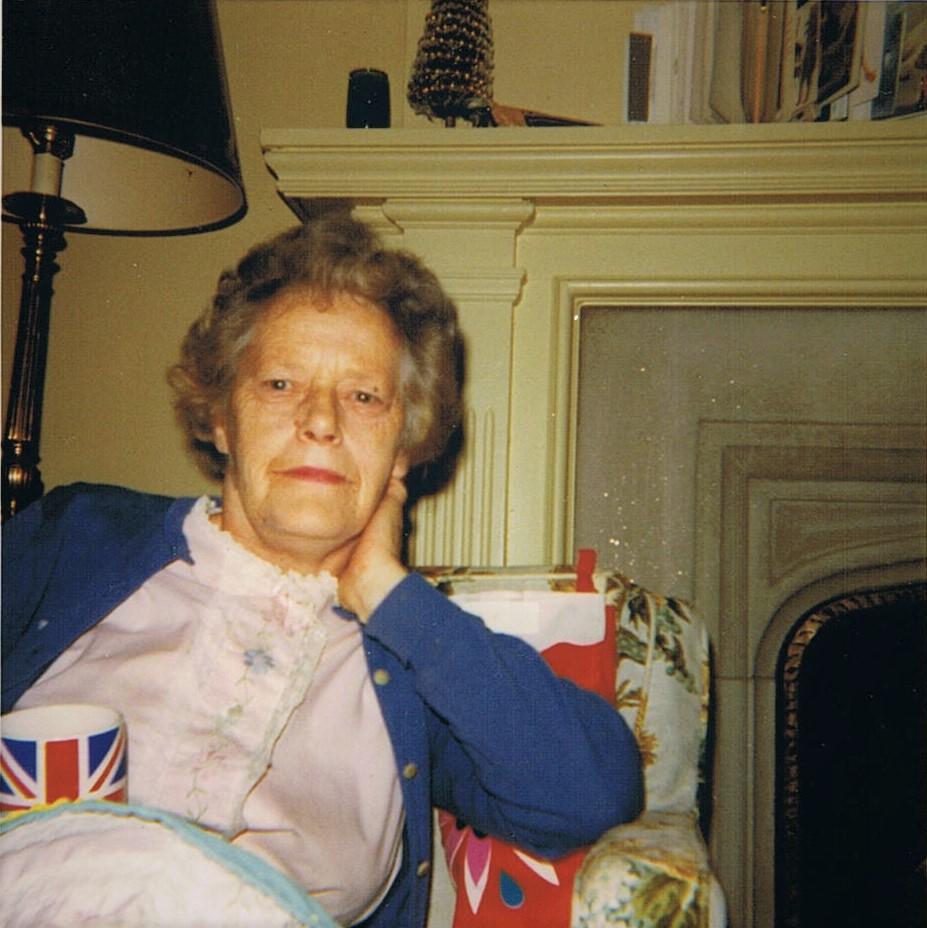 Woman sitting in a chair holding a Union Jack tea mug