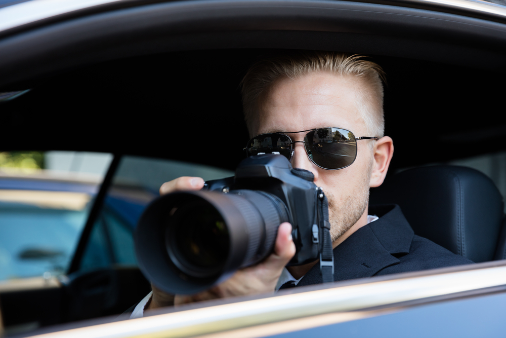Man sitting in car with sunglasses on, using a camera with a telephoto lens