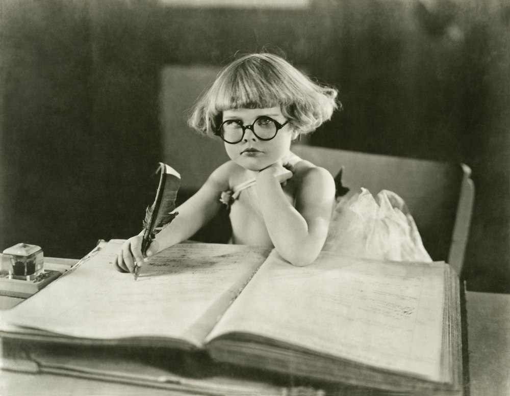 Young girl with glasses writing with a quill in a large book