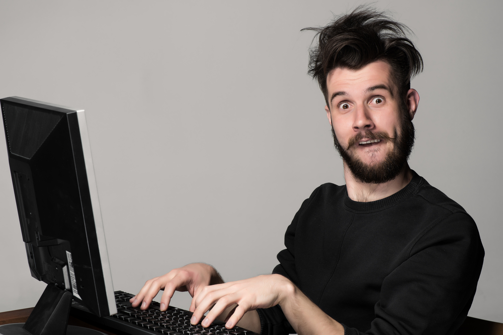 Guy typing at a computer with a wacky look on his face