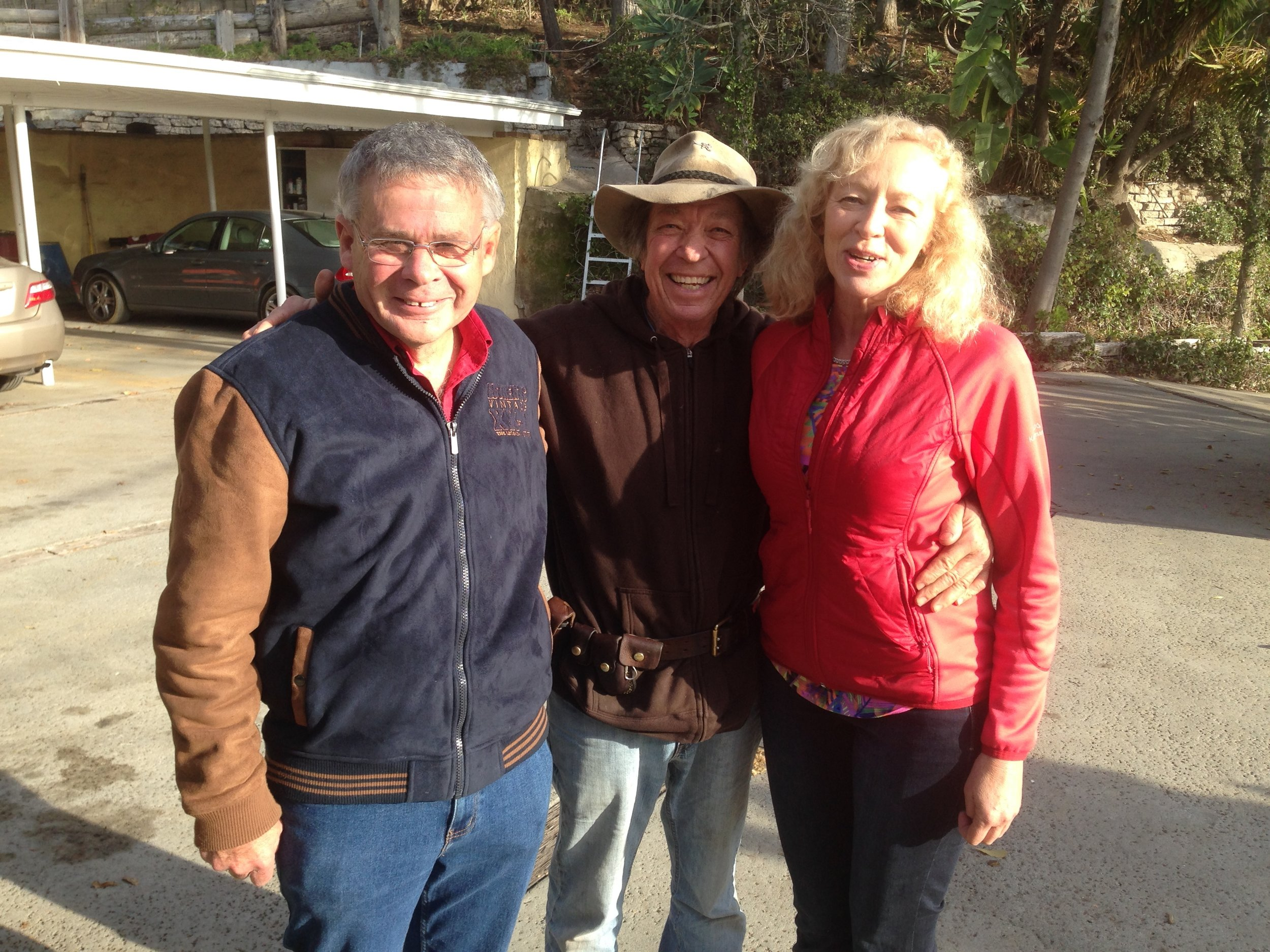 """COLIN VISITS WITH NEIL AND HIS WIFE CHRIS, ON COLIN'S RANCH IN MALIBU . THEY ALL MET 30 YEARS AGO WHEN COLIN FIRST STARTED PESTERING NEIL ABOUT WRITING A BOOK. COLIN DIDN'T BUY NEIL'S EXCUSE THAT HE WAS NOT A WRITER. AFTER WORKING AT IT FOR A COUPLE OF YEARS, NEIL DISCOVERED HE WAS INDEED A WRITER AND TODAY HE HAS A RUNAWAY BEST SELLER!! RECALLS CHRIS: """"COLIN, THERE WERE TIMES I WANTED TO KILL YOU! WRITING THIS BOOK WAS DRIVING US CRAZY. BUT NOW I JUST WANT TO HUG YOU FOR MAKING US DO IT. """""""