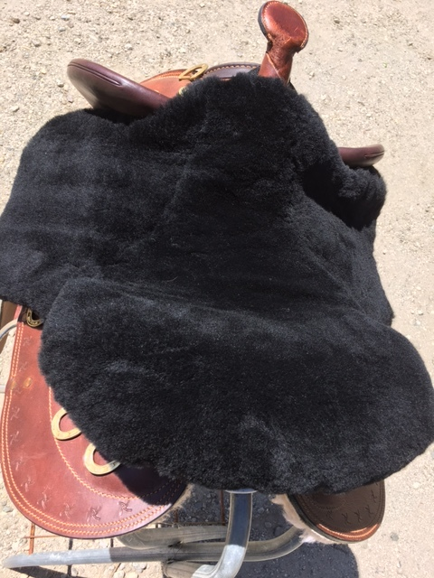 Merino sheepskin seat saver cut for an Aussie saddle. The seat saver secures to the saddle with elastic loops that slide in under the jockey flaps. Another long Velcro-closing strap pulls up from front to back in the under gullet of the saddle. Comes standard in black or off white, but for $50 custom fee it can be made from any color .