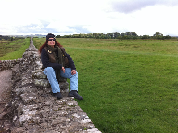 Pat Fish sitting on Hadrian's Wall in Scotland