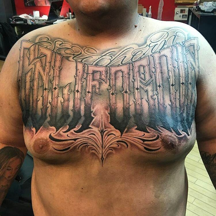 California block lettering on the chest black and gray tattoo.