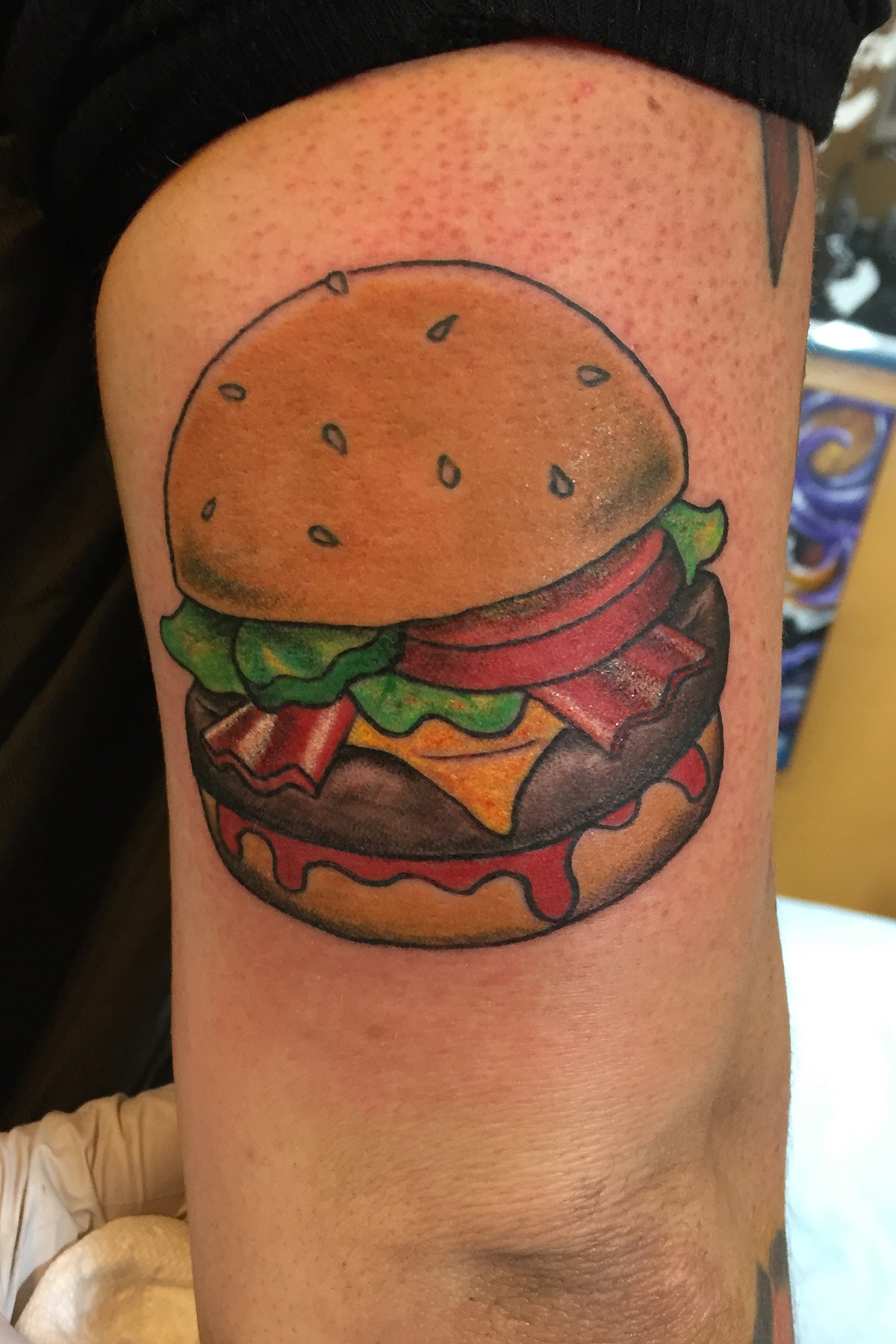 Bacon cheese burger on a sesame bun.  Half arm sleeve color tattoo.