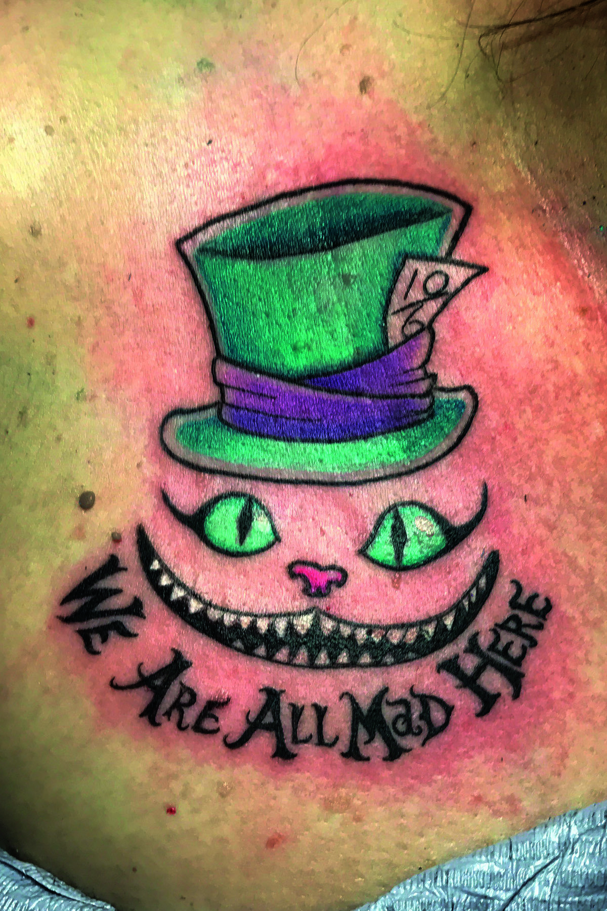 Cheshire cat smile and top hat, 'We are all mad here' in color. Below the collarbone tattoo.