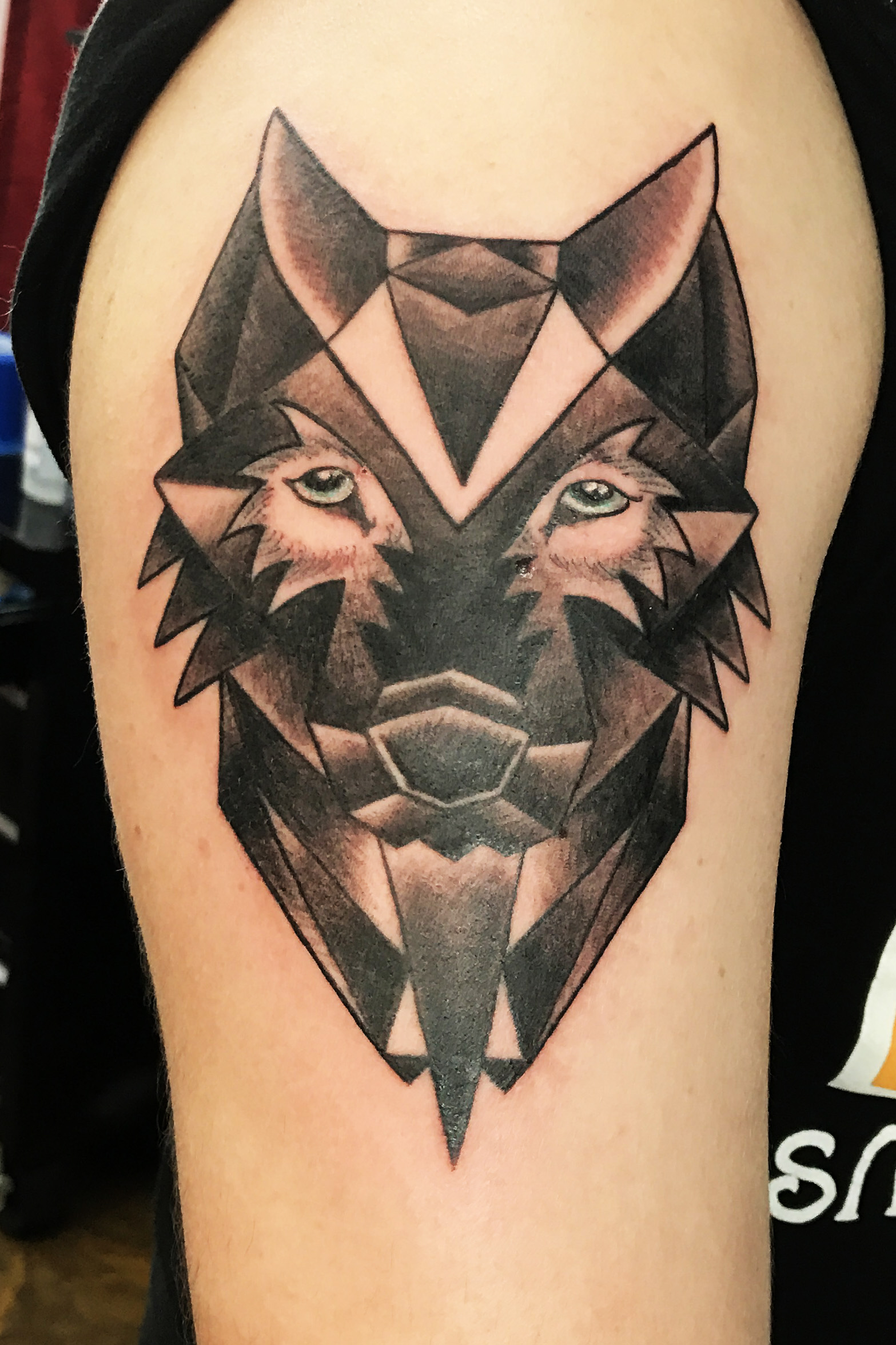 Geometrical Games of Thrones wolf, direwolves for the Stark family. Black and gray tattoo on upper arm half sleeve.