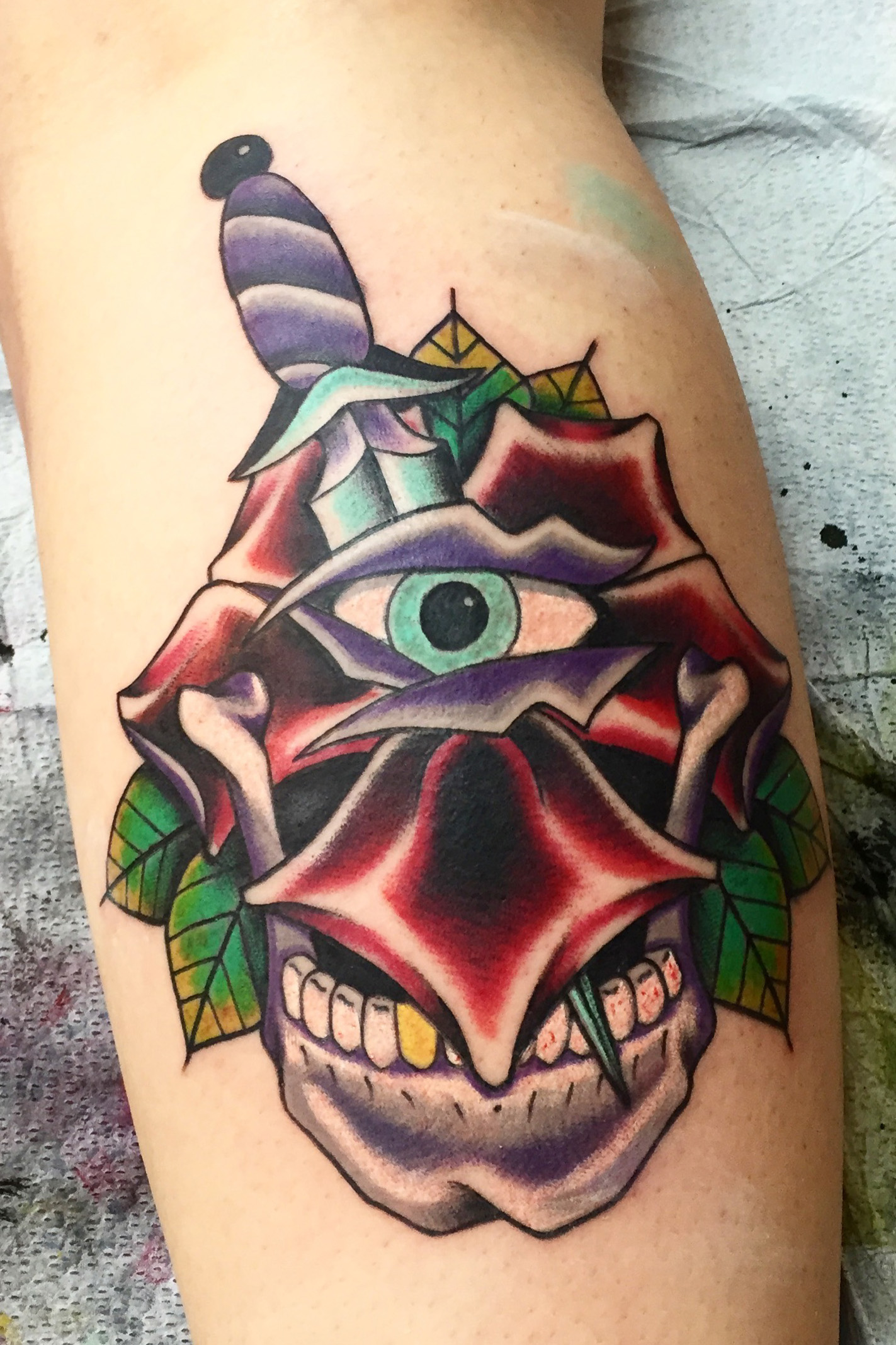 Cyclops skull with dagger and rose.  Neo Traditional color tattoo on leg half sleeve.