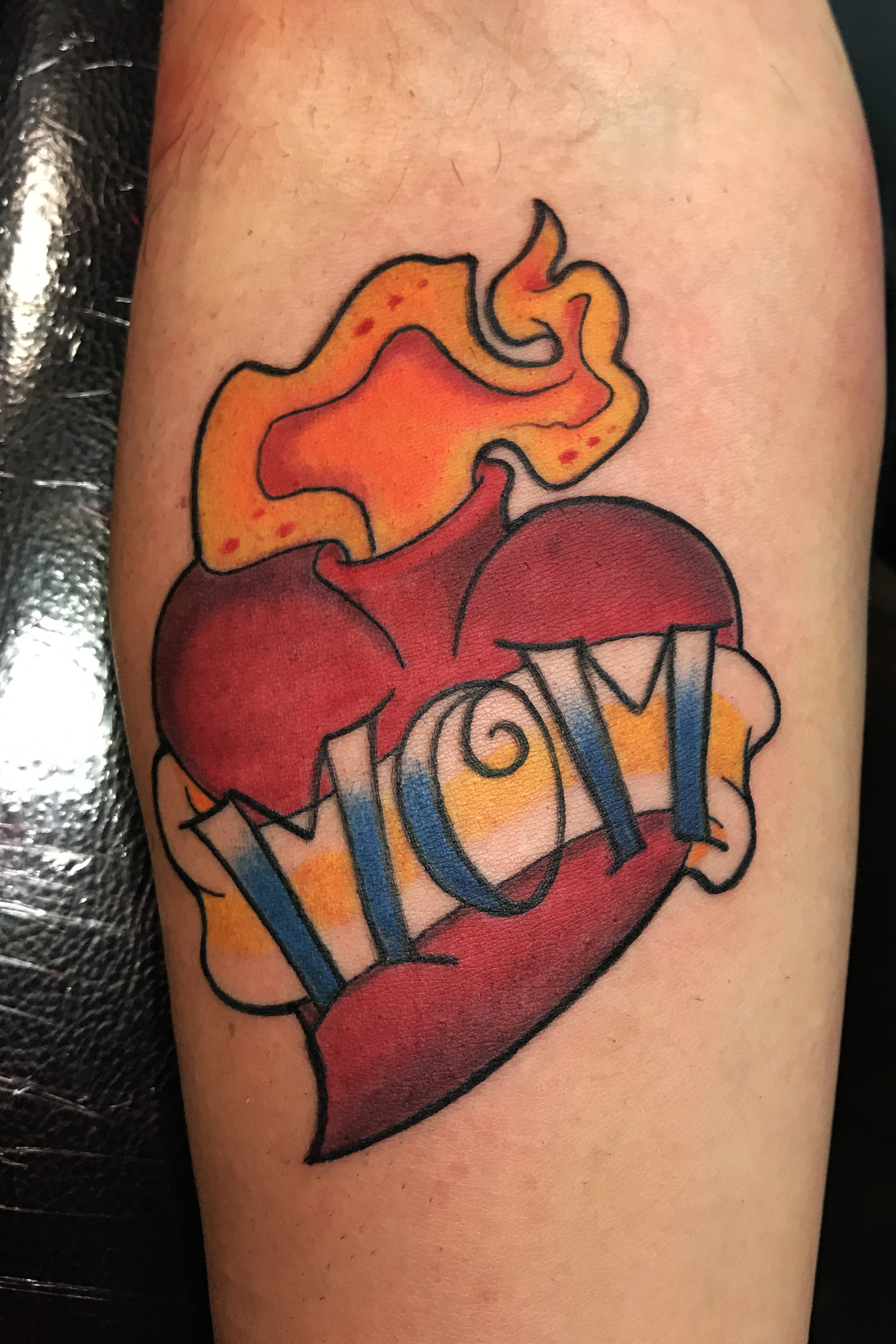 Heart for Mom. Sacred flaming heart. Mom lettering in a banner. Leg tattoo, traditional color.