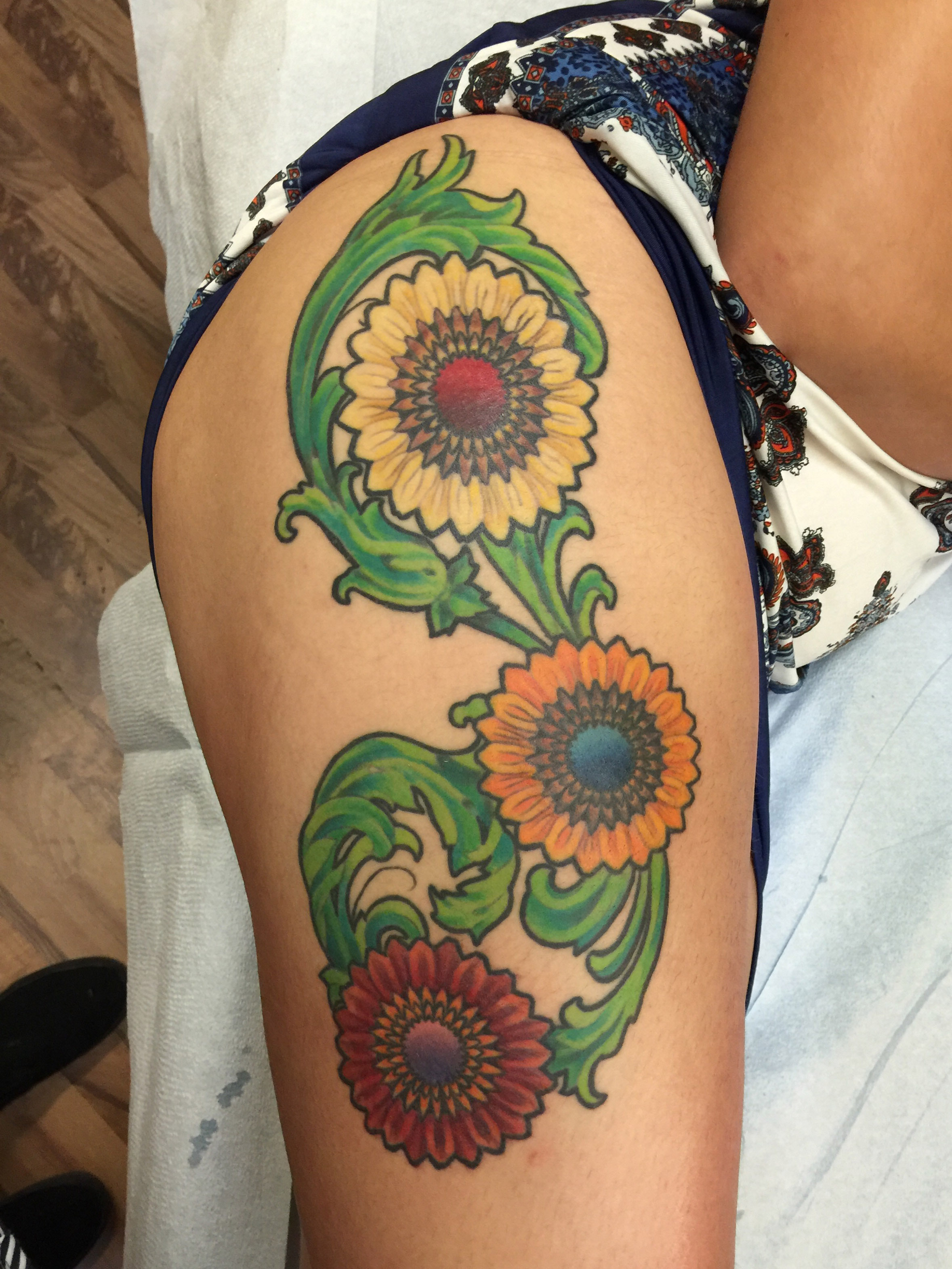 Neo Traditional colorful flowers on thigh tattoo.