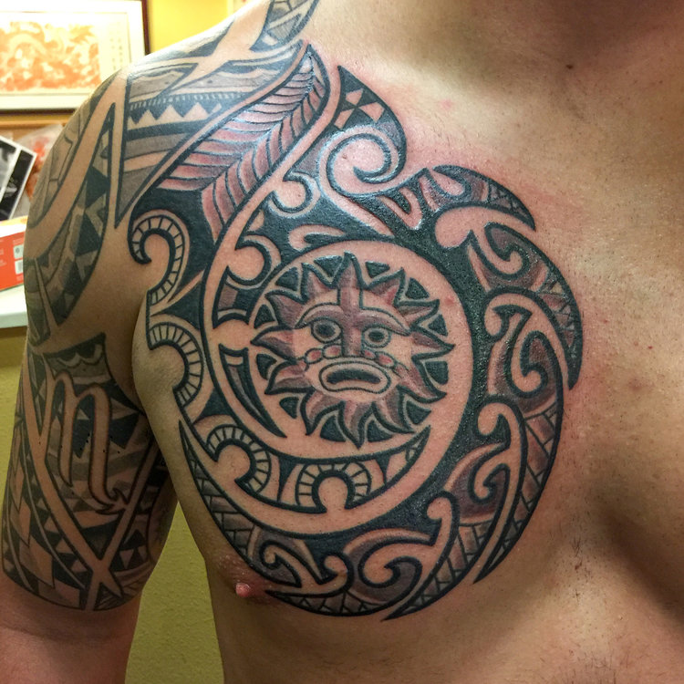 Tribal black and gray tattoo with sun on upper shouder and chest.