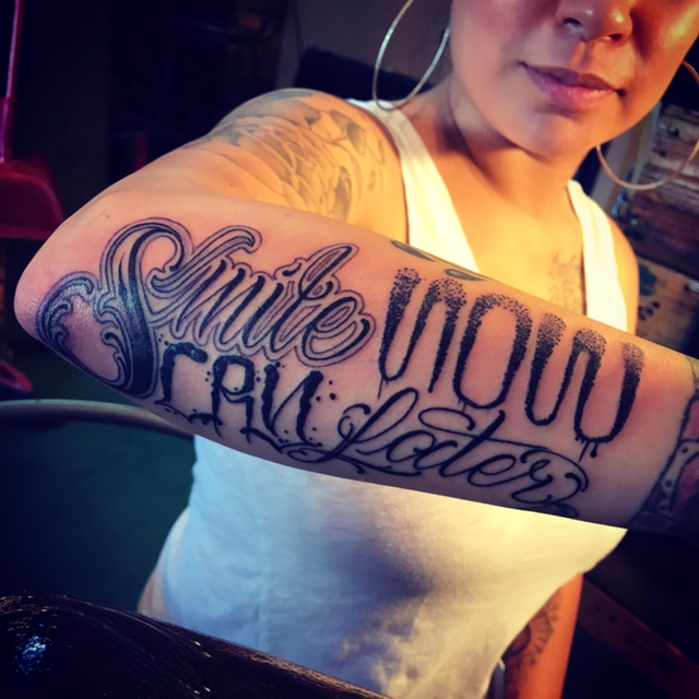 "Black and gray ""Smile Now Cry Later"" awesome lettering Tattoo. Side forearm half sleeve."