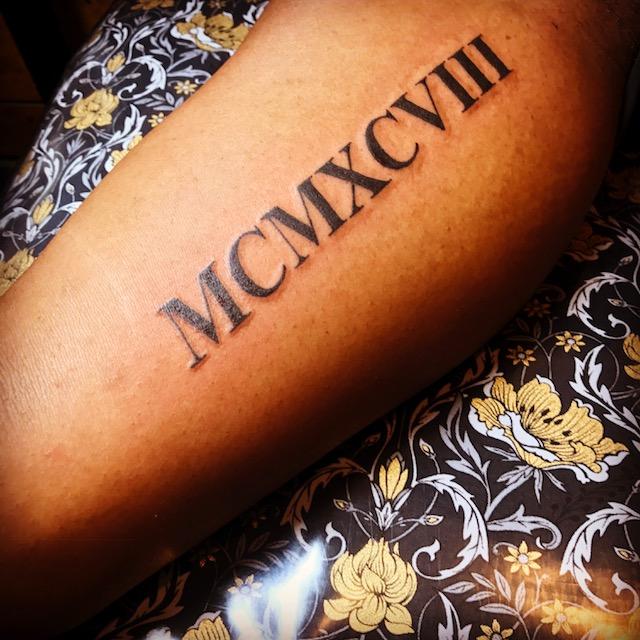 Roman Numerals black lettering tattoo. Half Sleeve forearm.