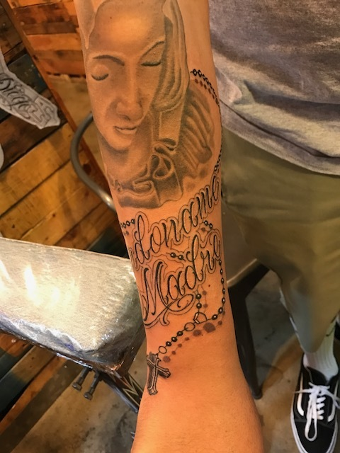 Fine detail lettering and rosary black and gray forarm tattoo
