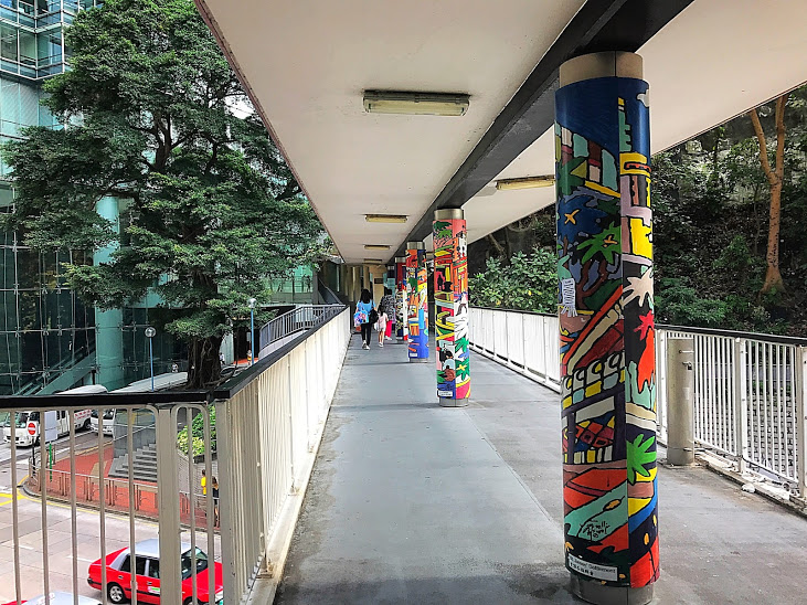 """In my neighborhood, Wan Chai, I came across an Open Air Art Gallery on a footbridge above one of the major roads. Over 20 pillars painted beautifully with a variety of colors and shapes. The purpose of the initiative was to depict """"50 Scenes of Wan Chai"""" past and present and bring beauty throughout the neighborhood. """"500 volunteers compromising of young children, elderly and disabled participated in the coloring of the new artwork... to demonstrate the cohesiveness and harmony of the Wan Chai community."""""""