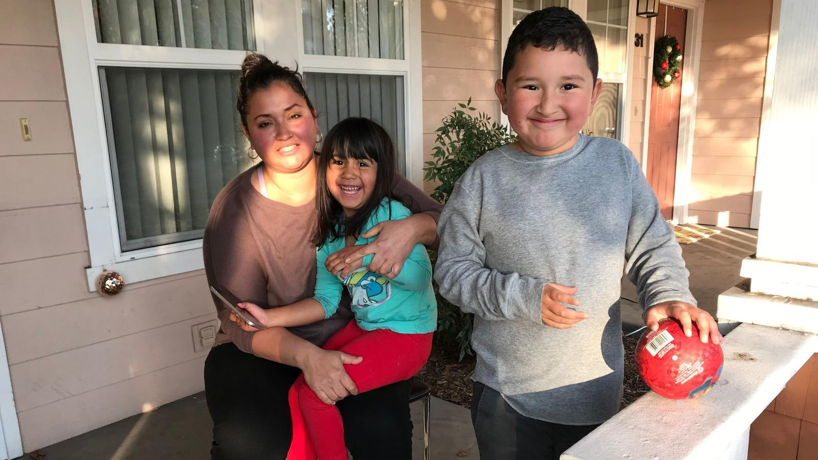 After spending two months sleeping in a friend's living room, the Alvarez family of Calistoga, who lost their home and their jobs, found a rent-subsidized condo in Cotati. Here, Claudia, 34, sits with children Sofia, 4, and Steven, 7, on their new front porch. (Robin Abcarian / Los Angeles Times)