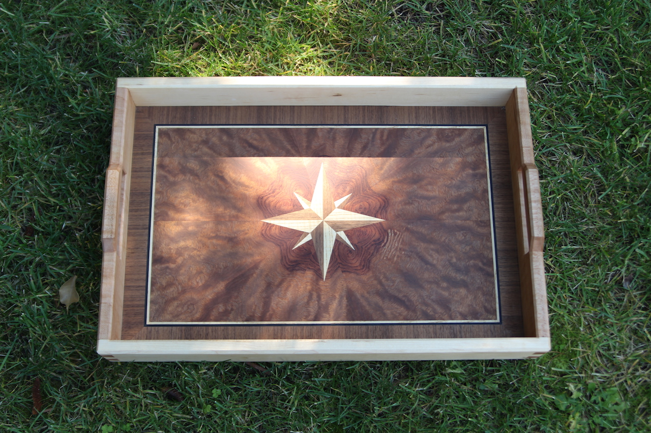 Serving tray made of Waterfall Bubinga, Maple, Walnut and Blackwood veneer for the pannel and Birdseye Maple for the handles and sides.