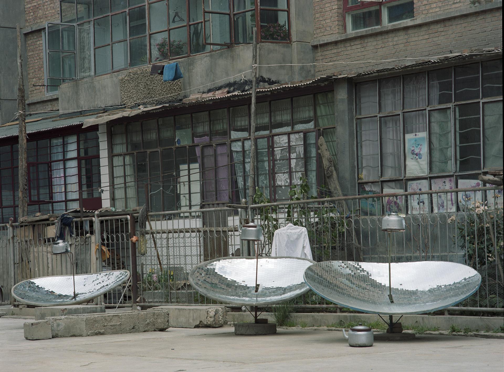2007 Qinghai - solar watercookers in from of a Tibetan housing block in Tongren.