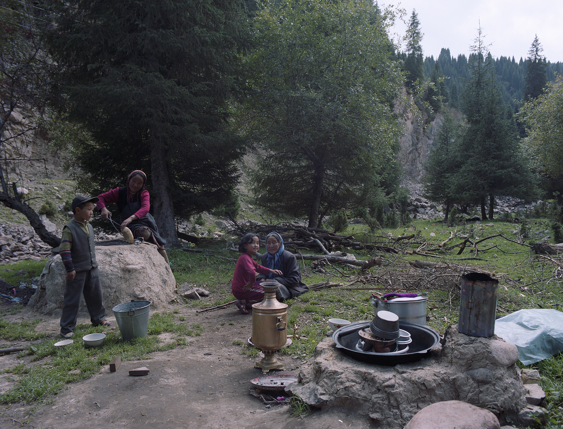 2007 Xinjiang - around the yurt with the family. The girl left id baking bread in the traditional stove built from local stones and mud.