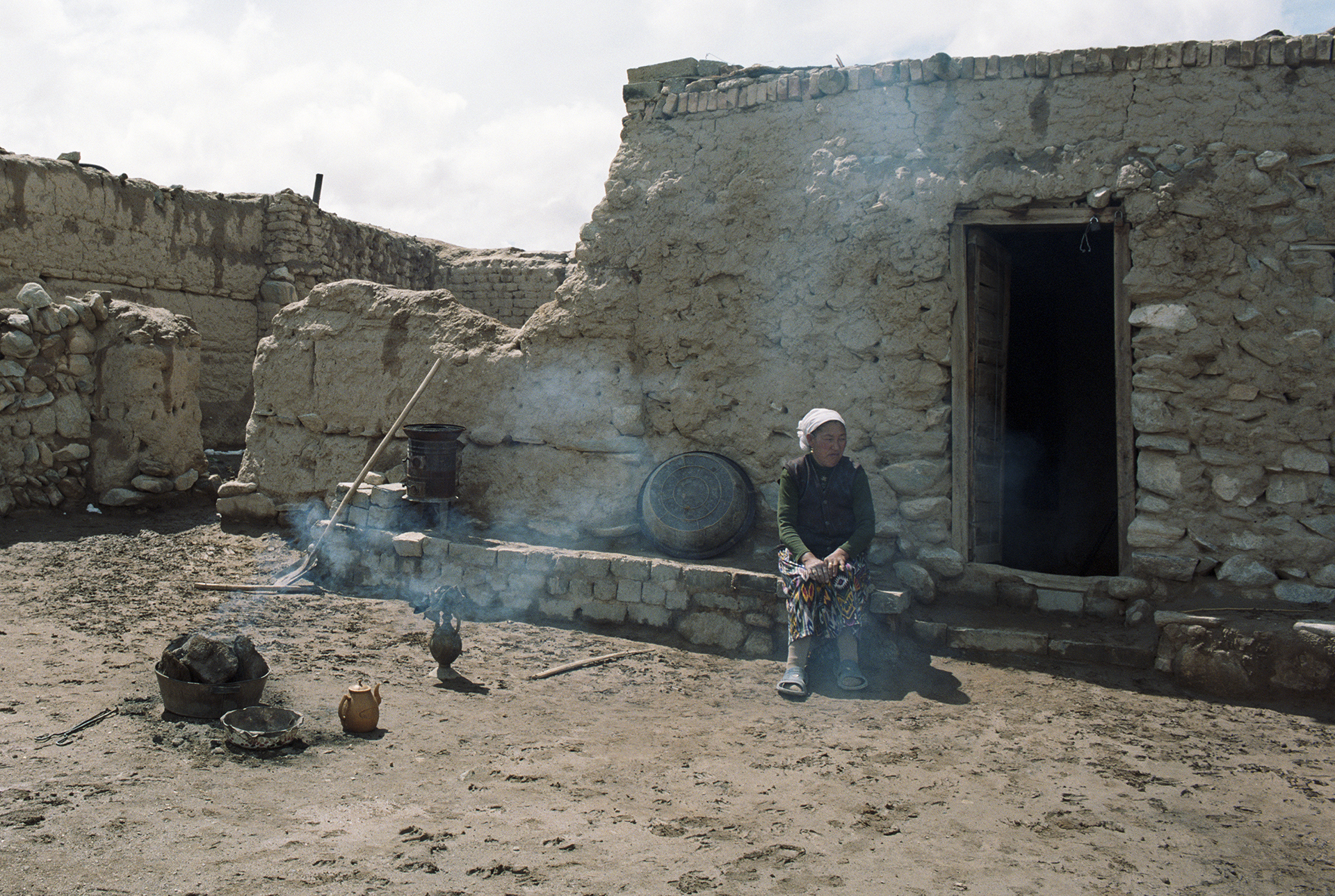 2007 Xinjiang - woman out in her yard to oversee the baking of the bread.