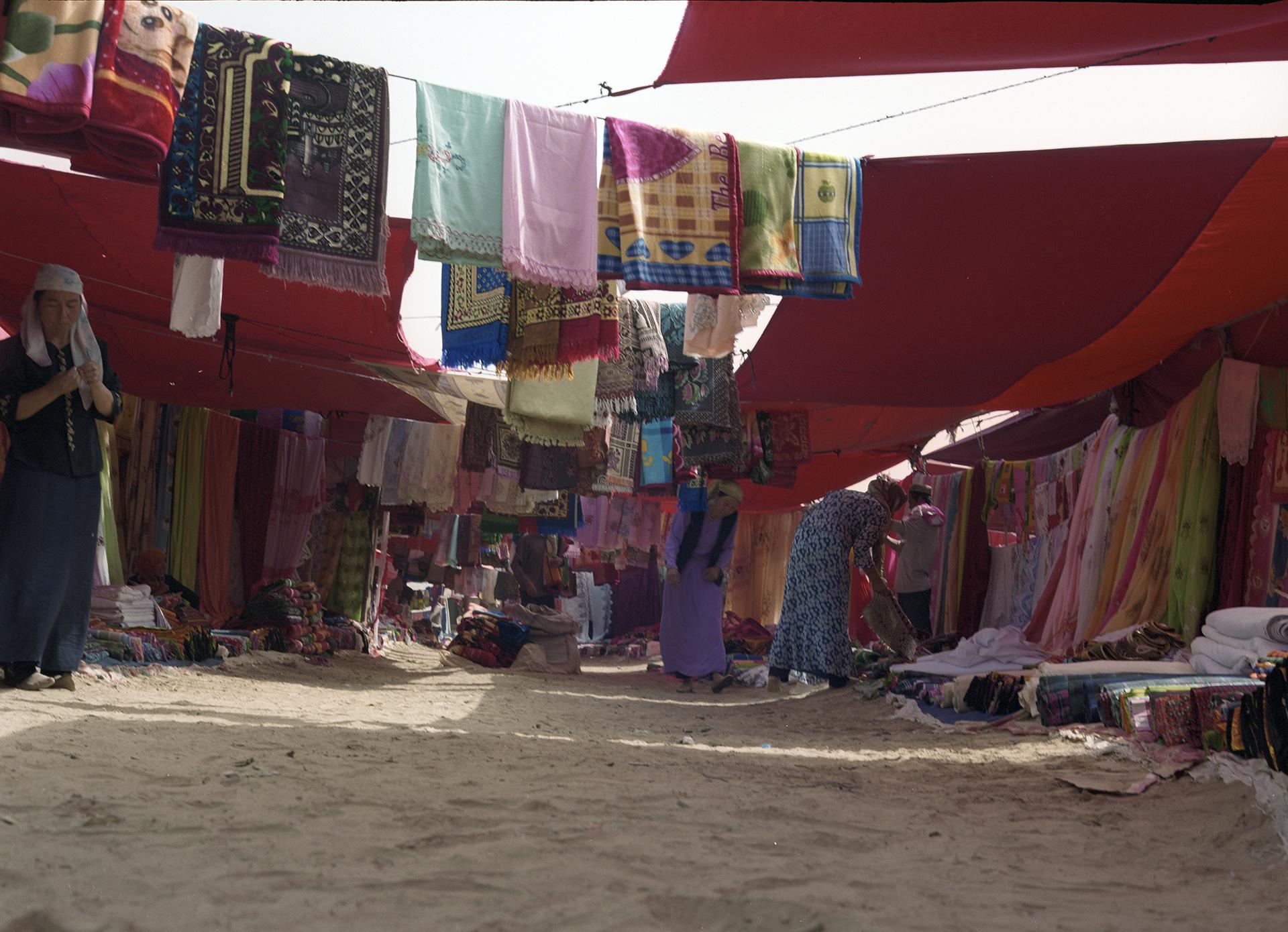 2007 Xinjiang - local market at Kuriyä. A full lane of women's delight.