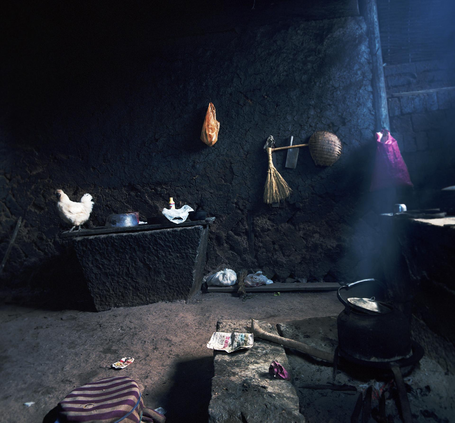 2008 Yunnan - a white chicken in a very black kitchen.