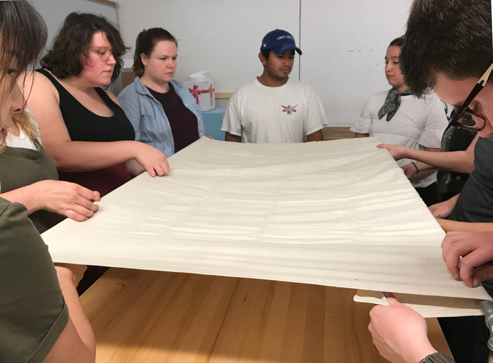 Pictured: Students in the  Social Fabric: Inventive Surface class  squeeze shoulder-to-shoulder around a makeshift embroidery frame to begin a group embroidery sampler in order to learn a variety of embroidery stitches together using large scale needles and threads.
