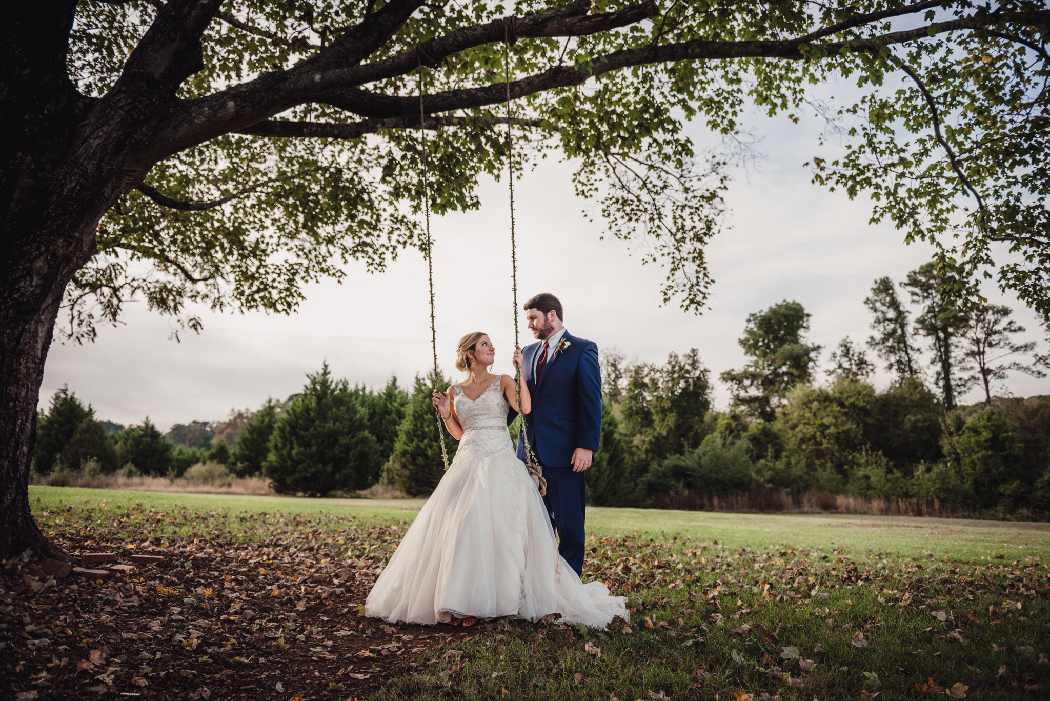 bride-sitting-on-a-swing-with-her-groom.jpg