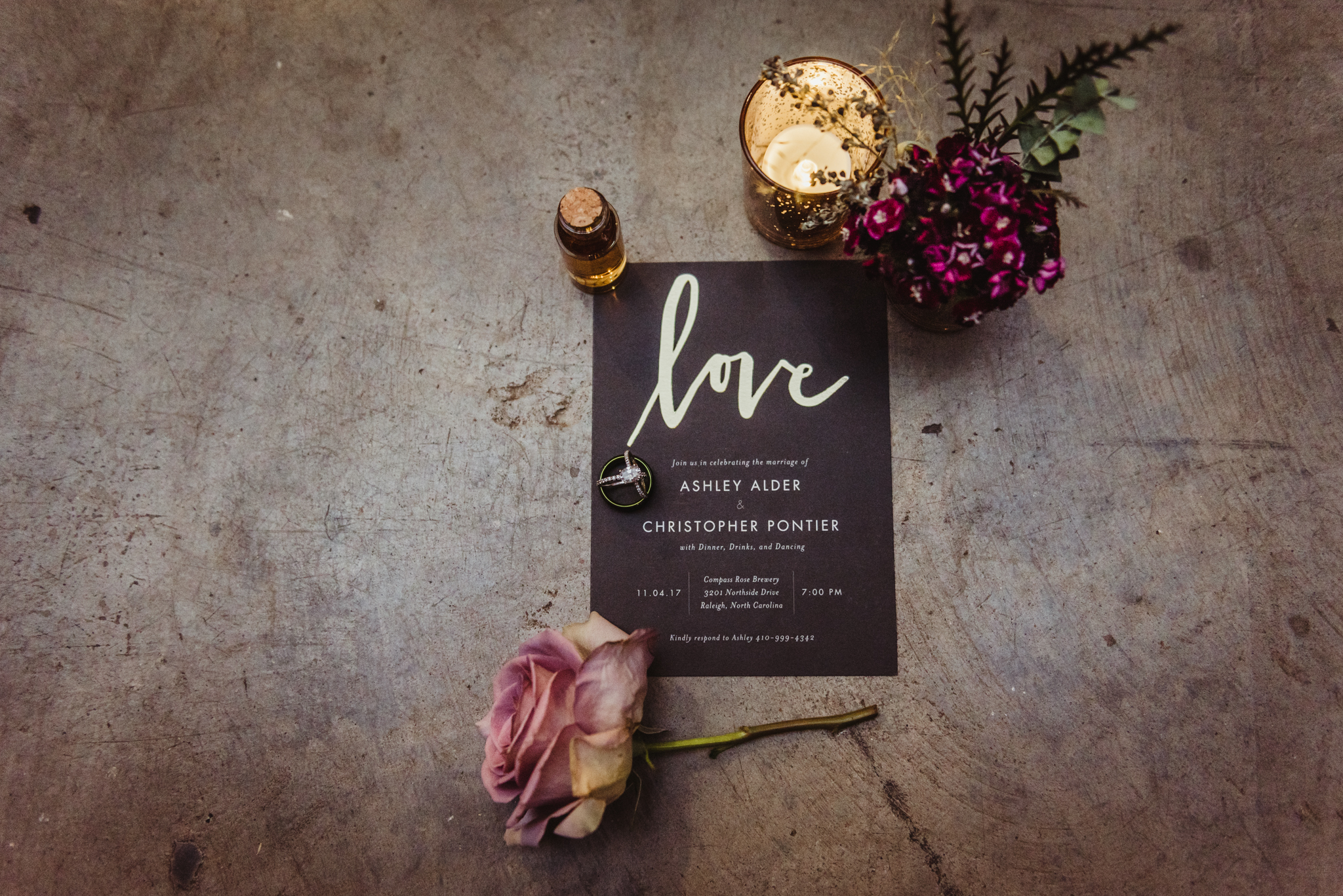black-and-gold-wedding-invitation-and-rings-with-purple-flowers.jpg