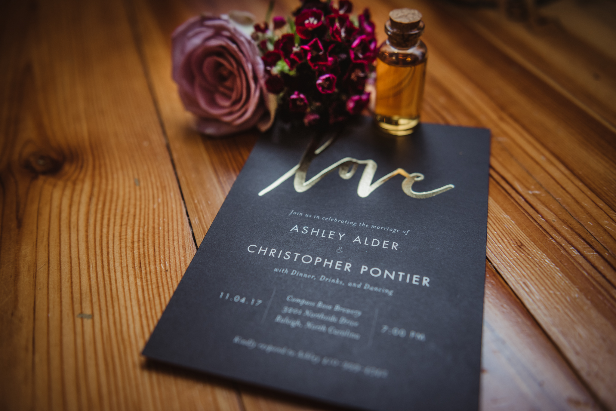 black-and-gold-wedding-invitation-with-shot-and-purple-flowers.jpg
