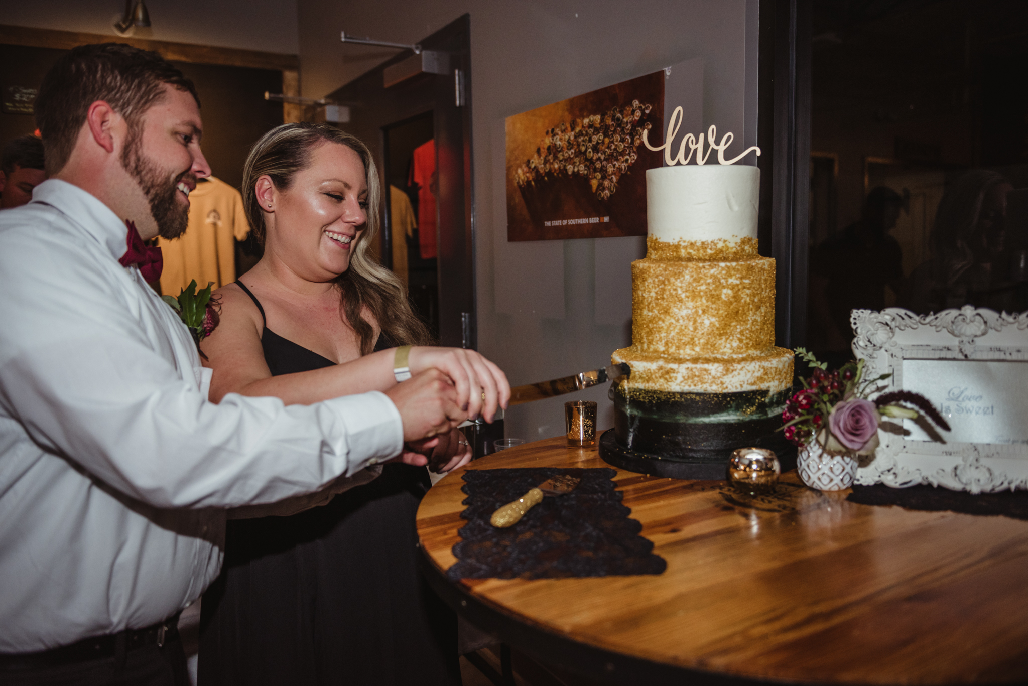 bride-and-groom-cutting-the-gold-and-black-cake.jpg