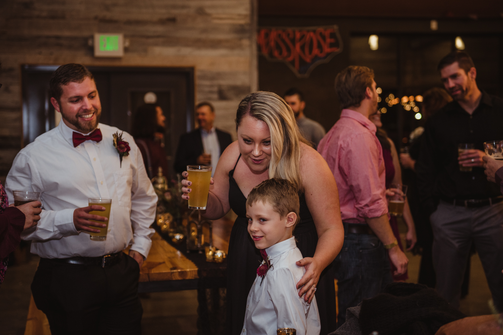 the-bride-and-groom-hug-their-son-at-the-reception.jpg