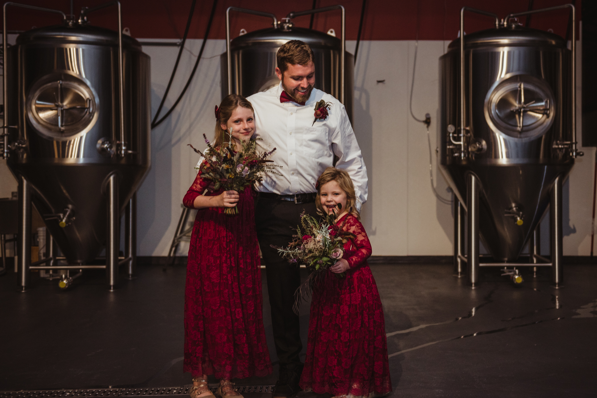 the-groom-with-his-daughters-pose-for-a-picture-with-the-vats-of-beer-behind-them.jpg