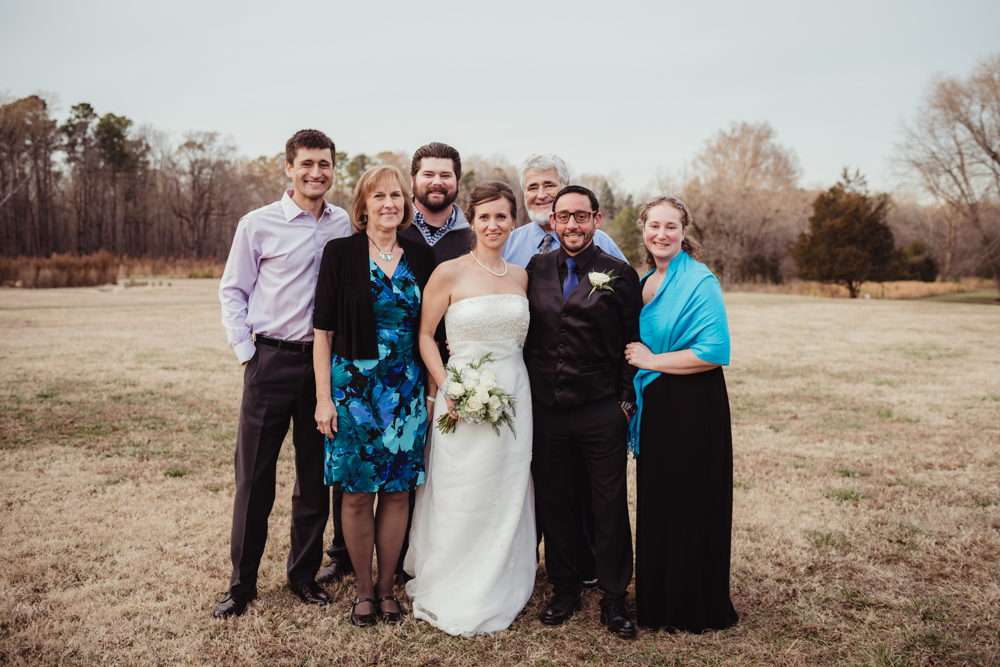 the-bride-and-groom-with-the-brides-family-in-the-park-in-Raleigh.jpg