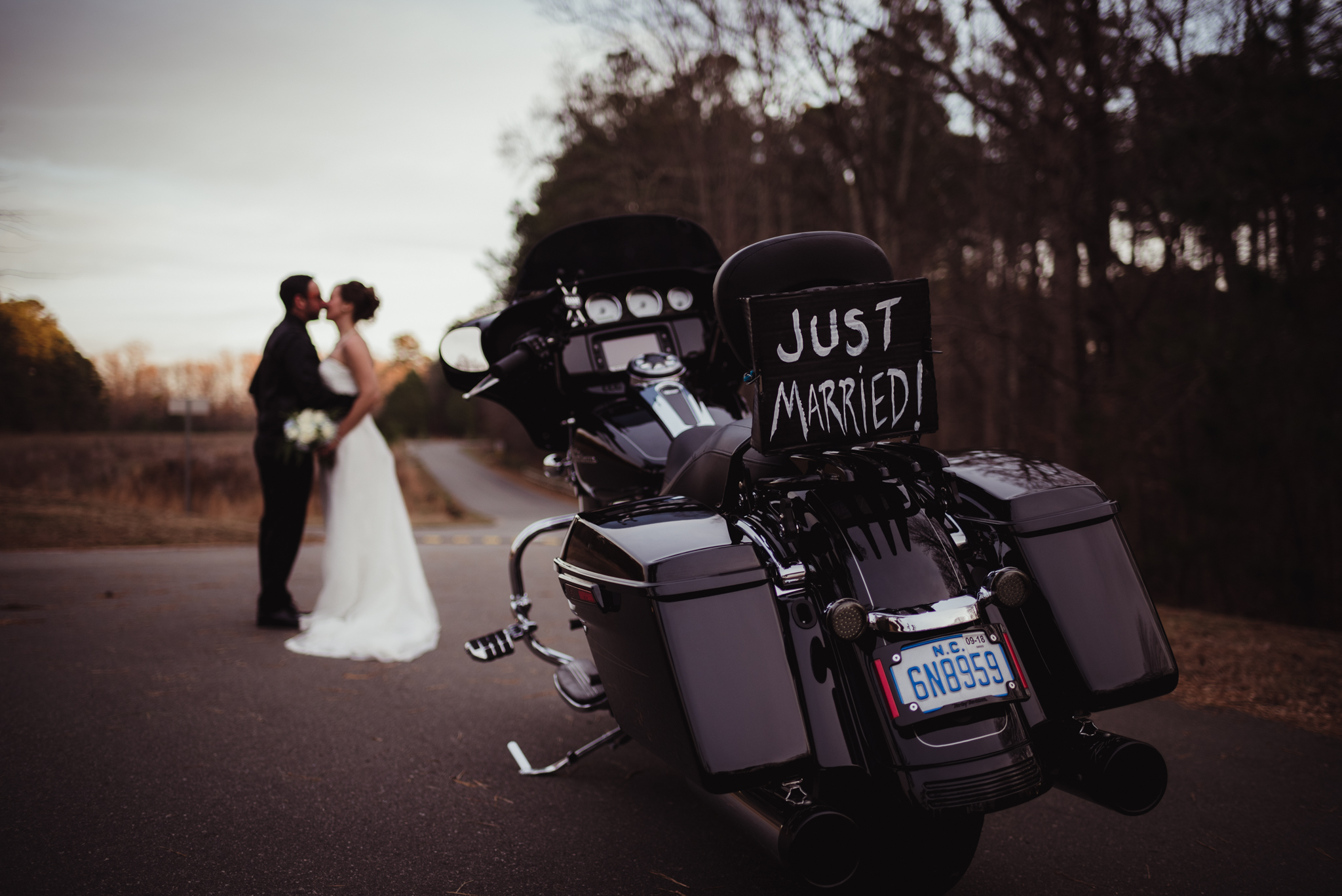 the-bride-and-groom-pose-near-their-motorcycle-after-getting-married-in-raleigh.jpg