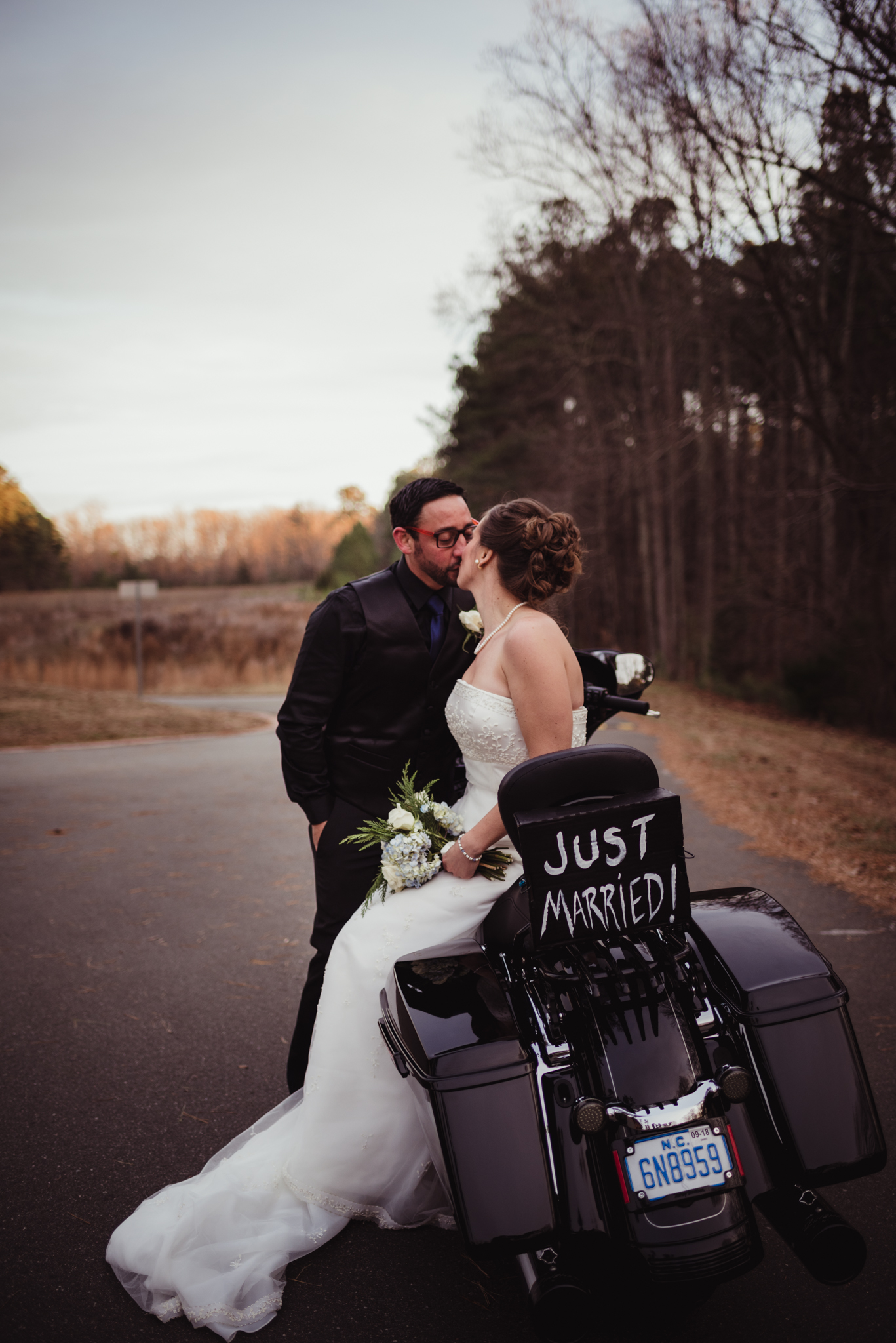 the-bride-and-groom-steal-a-kiss-on-their-bike-after-getting-married-in-raleigh.jpg