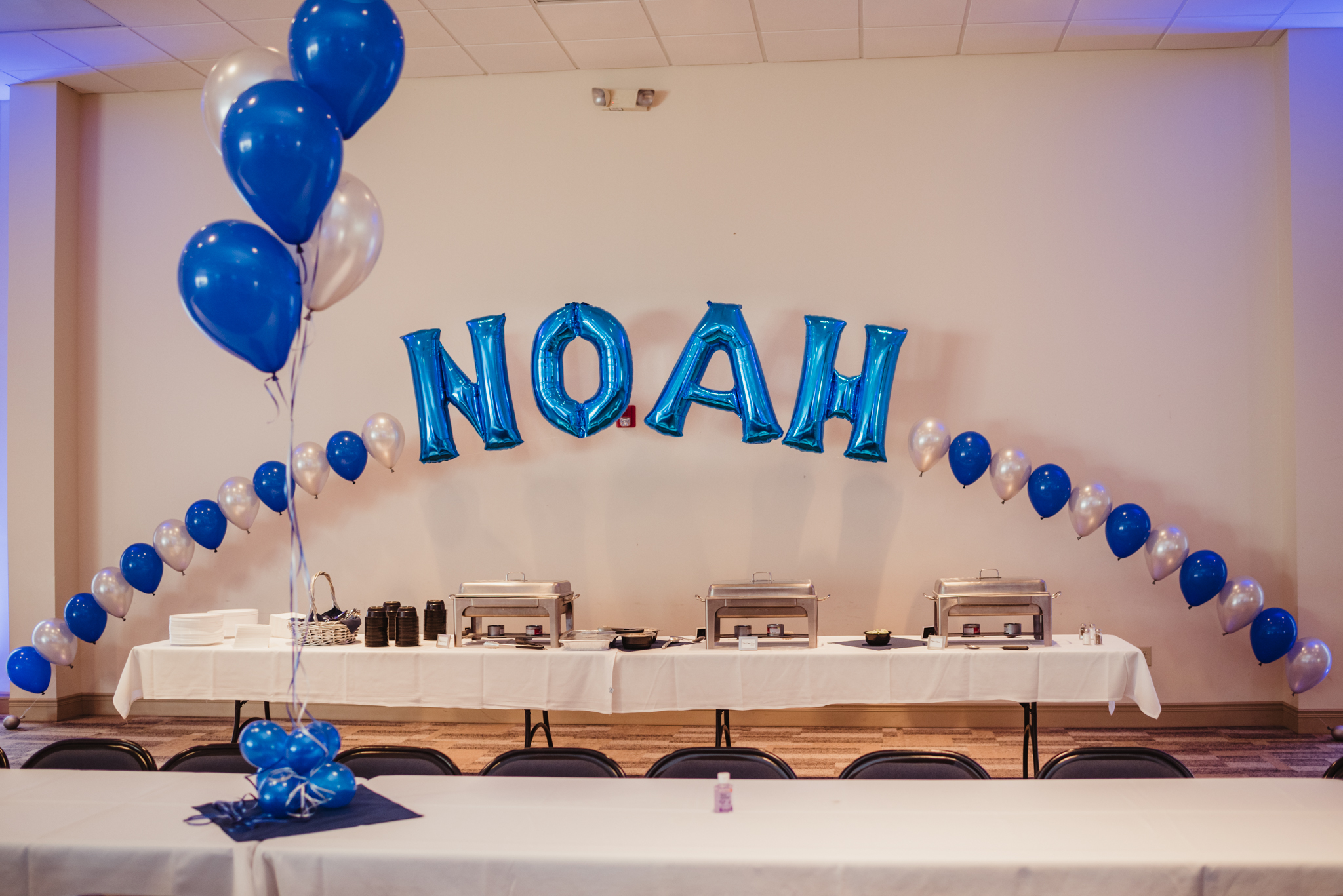 Blue and silver balloons that spell out Noah's name adorn the back of the celebration space at Temple Beth Or.