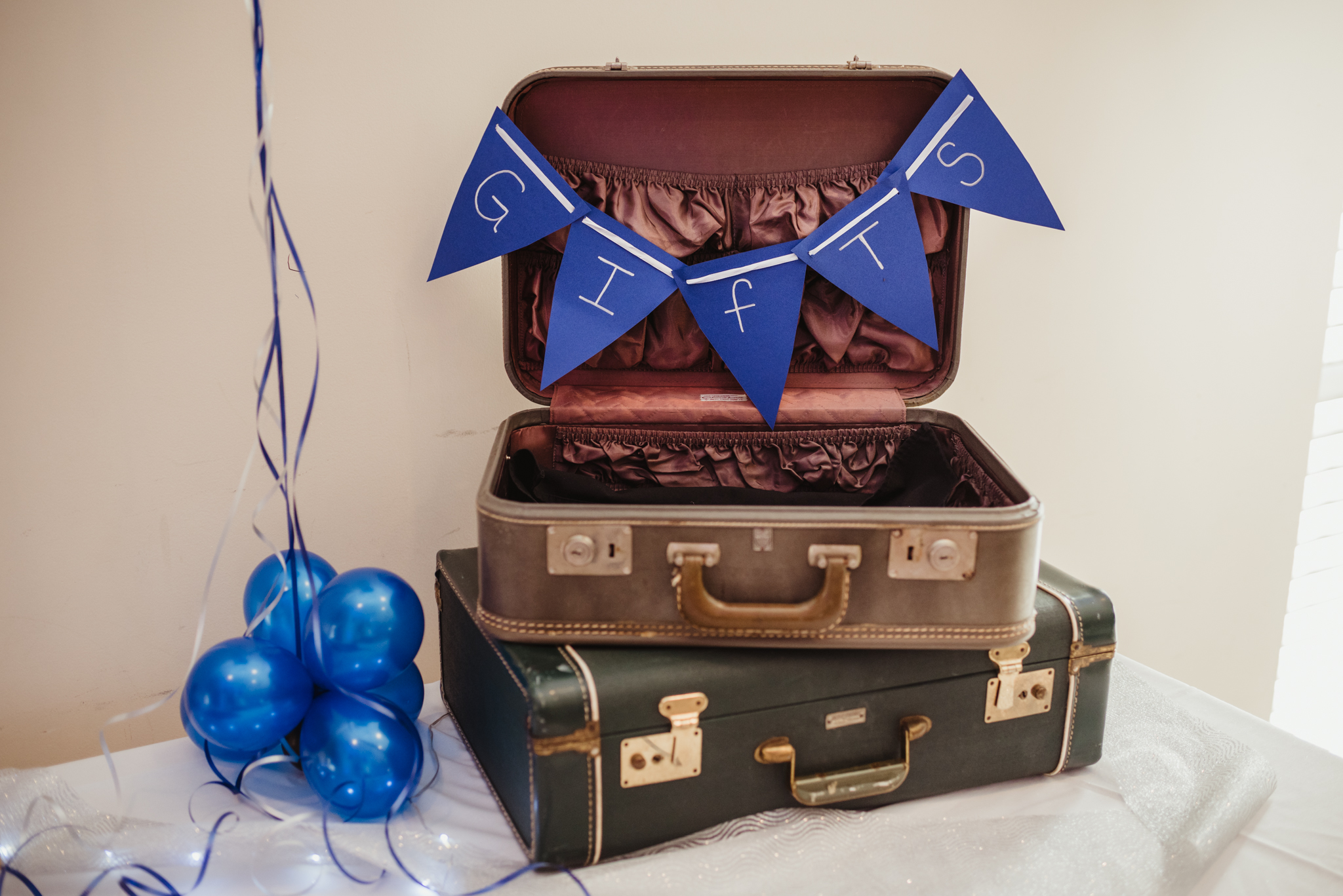 Balloons and suitcases, adorned with a blue banner, are a perfect place for guests to place gifts and cards for the bar mitzvah boy.