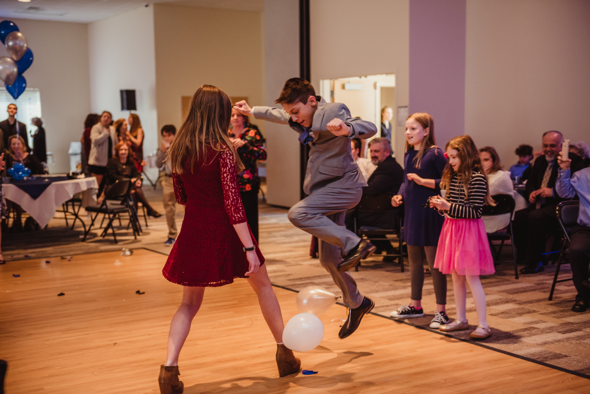 Noah tries to pop someone else's balloon during a bar mitzvah game at Temple Beth Or in Raleigh.