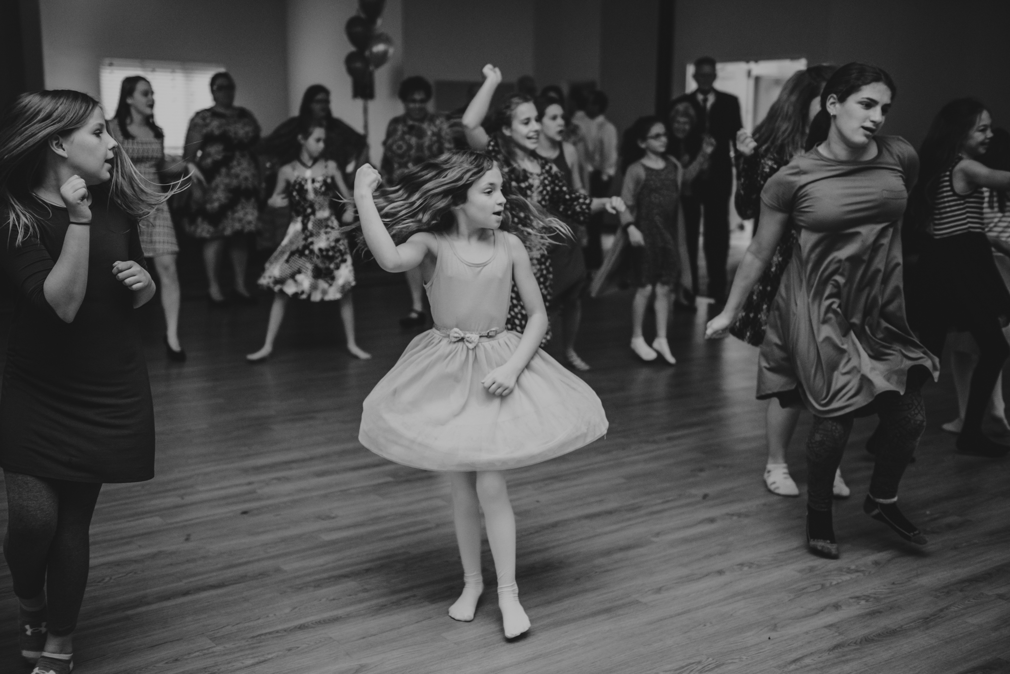 A girl spins around while dancing during the mitzvah reception at Temple Beth Or in Raleigh.