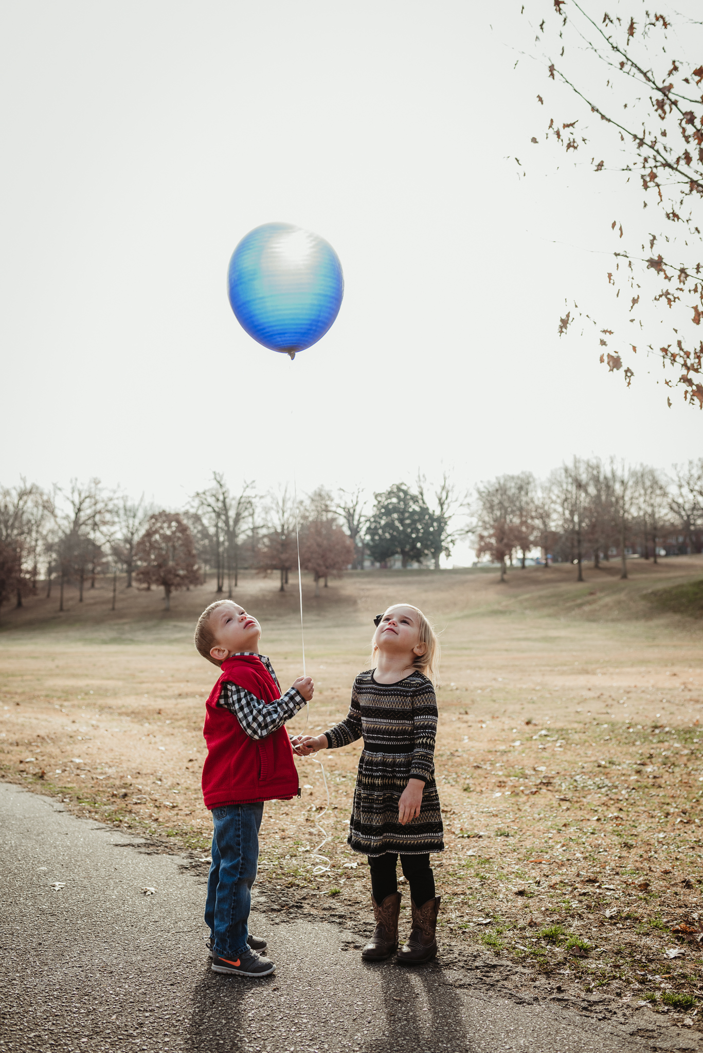 Twin three year old siblings look up at and hold a blue balloon during their family photos, the blue balloon representing their brother who passed away as a baby.