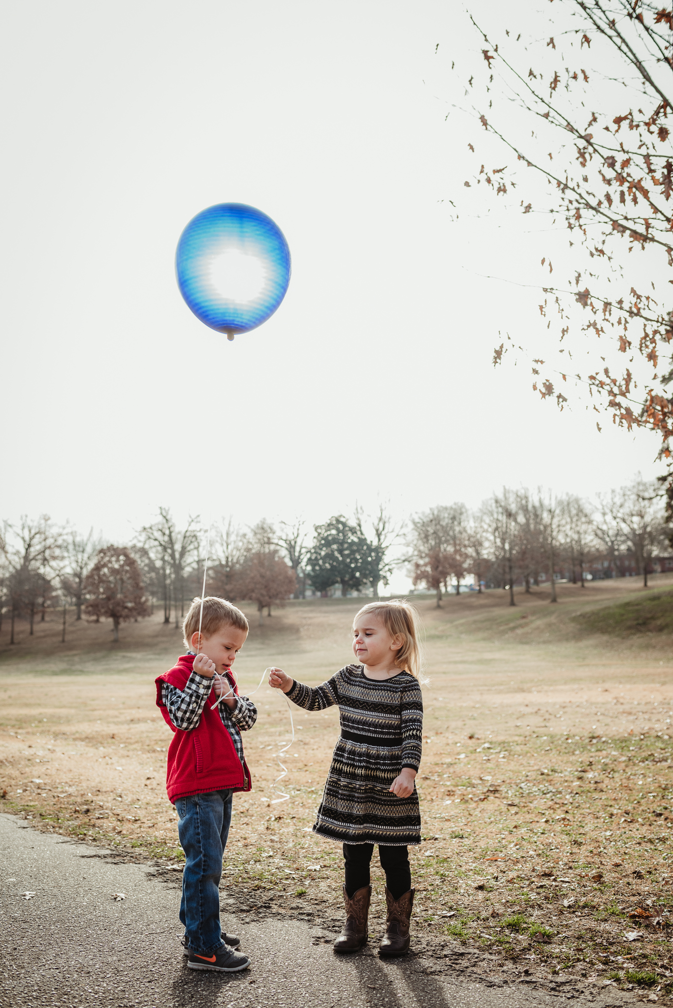 Twin three year old siblings fight over who gets to hold onto a blue balloon during their family photos, the blue balloon representing their brother who passed away as a baby.
