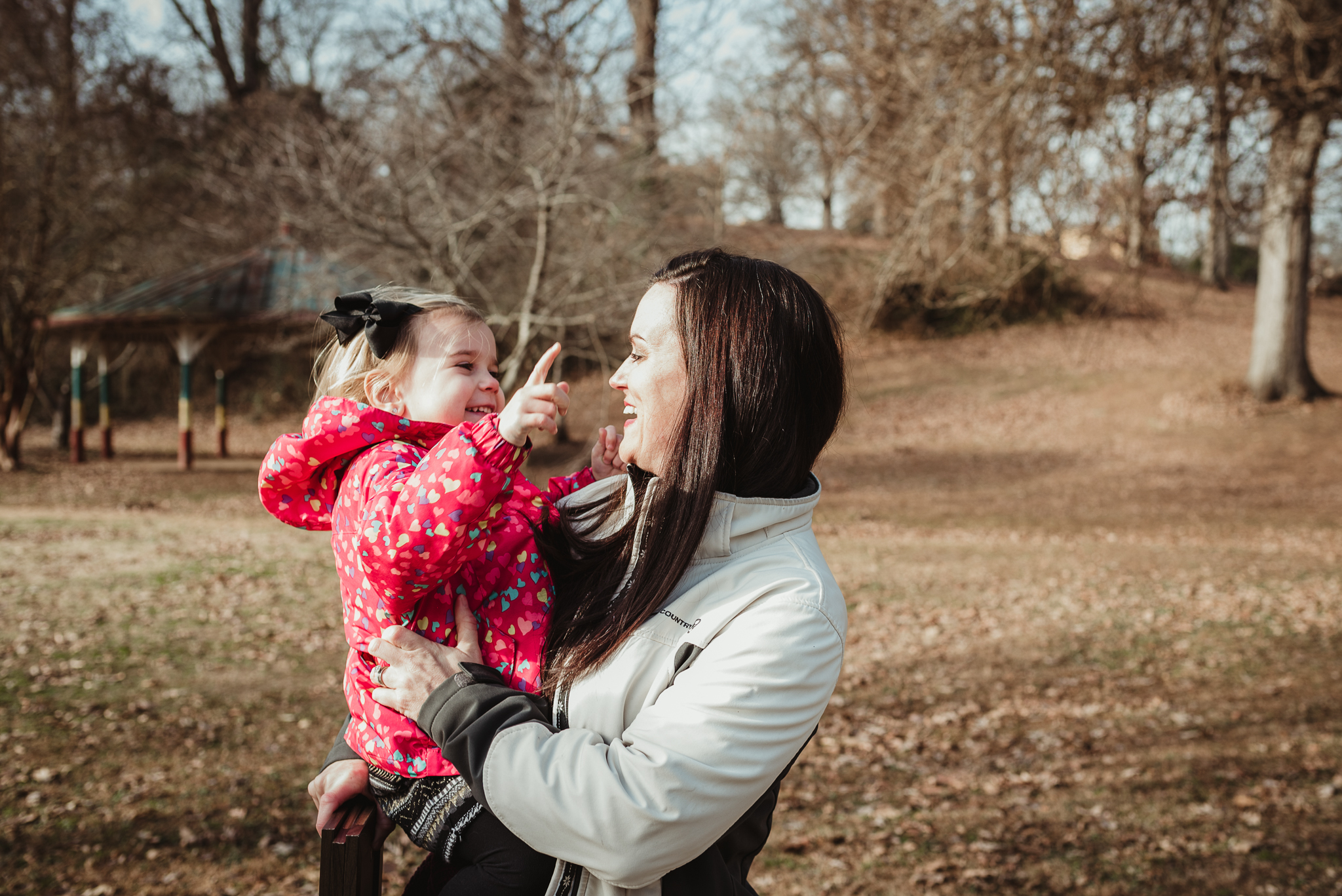 The three year old girl gets held by Mommy, while they point to the sky during their family session in Raleigh, North Carolina.