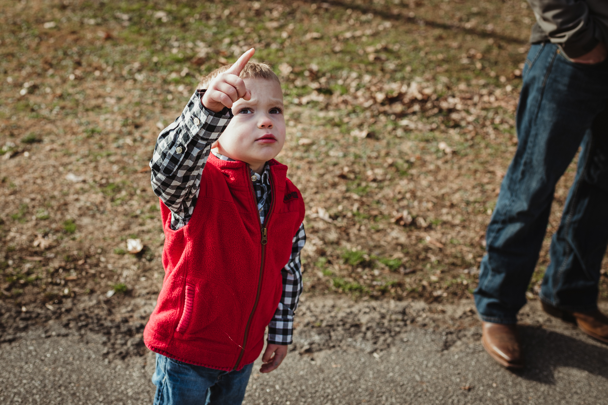 The three year old boy points to the sky during his family photo session in Raleigh, North Carolina.