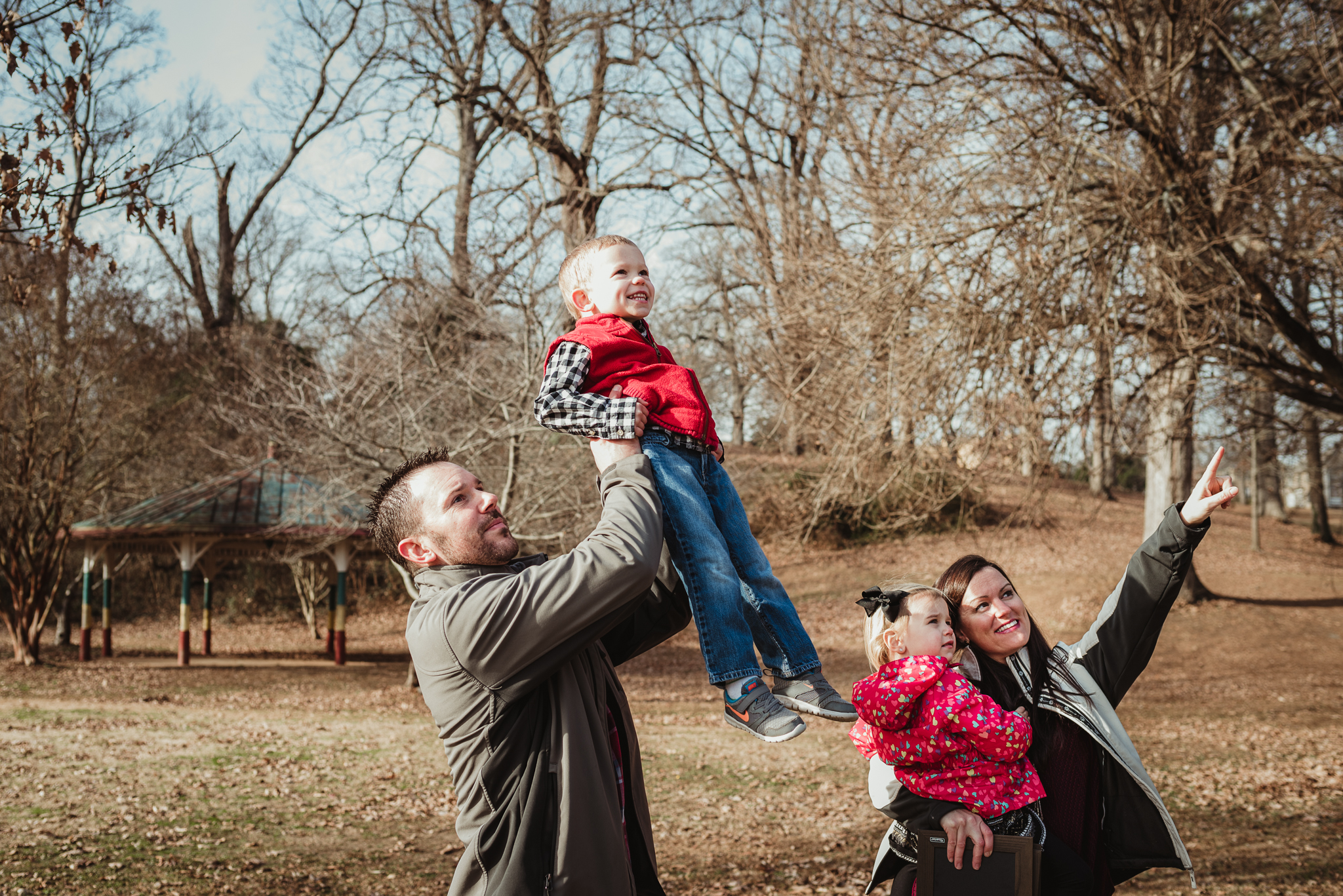 The family stares and points to the sky during their family photo session at Dorothea Dix Park in Raleigh, North Carolina.