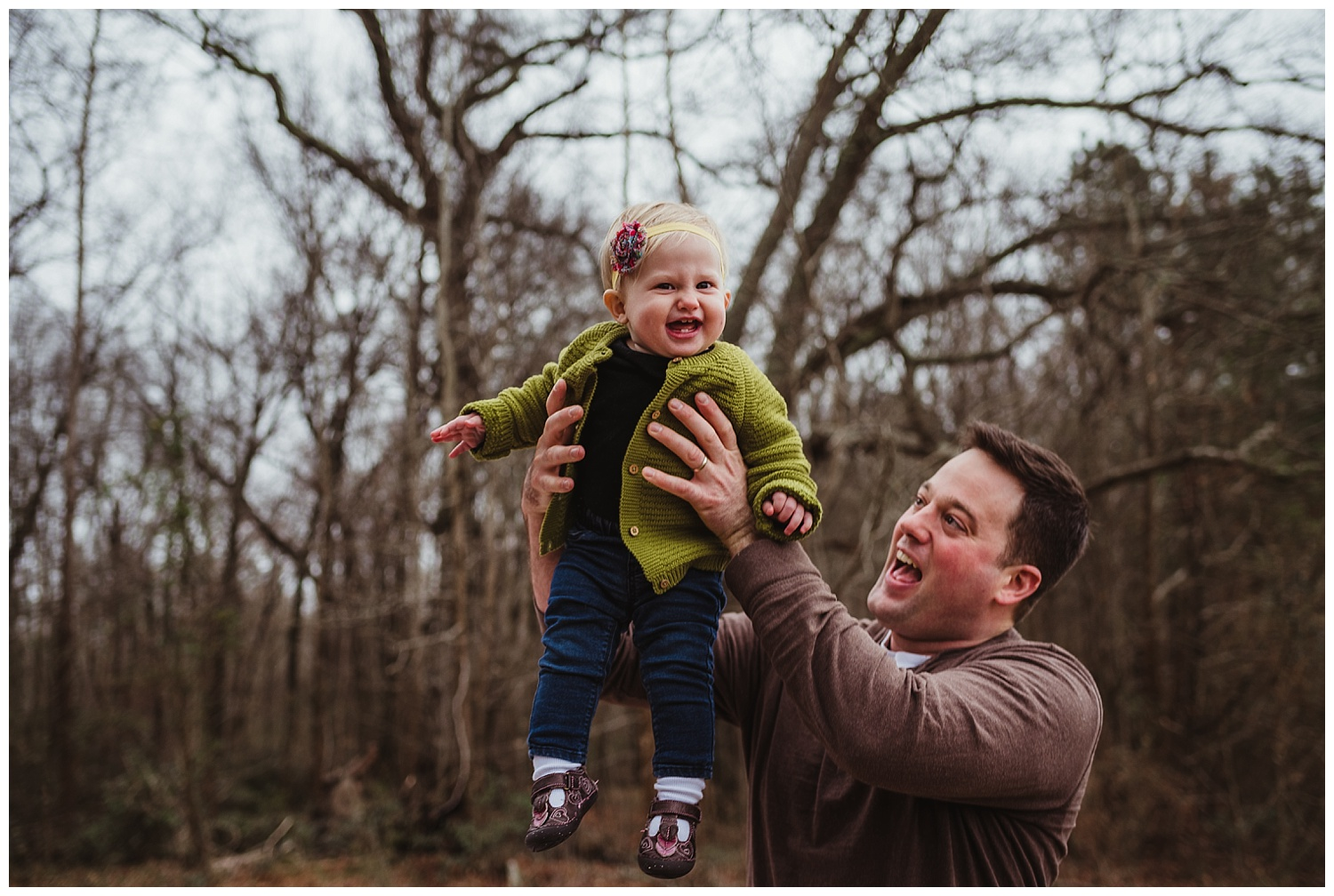 The dad lifts his baby daughter in the air like Simba from the Lion King during the family photo session in Wake Forest, North Carolina.