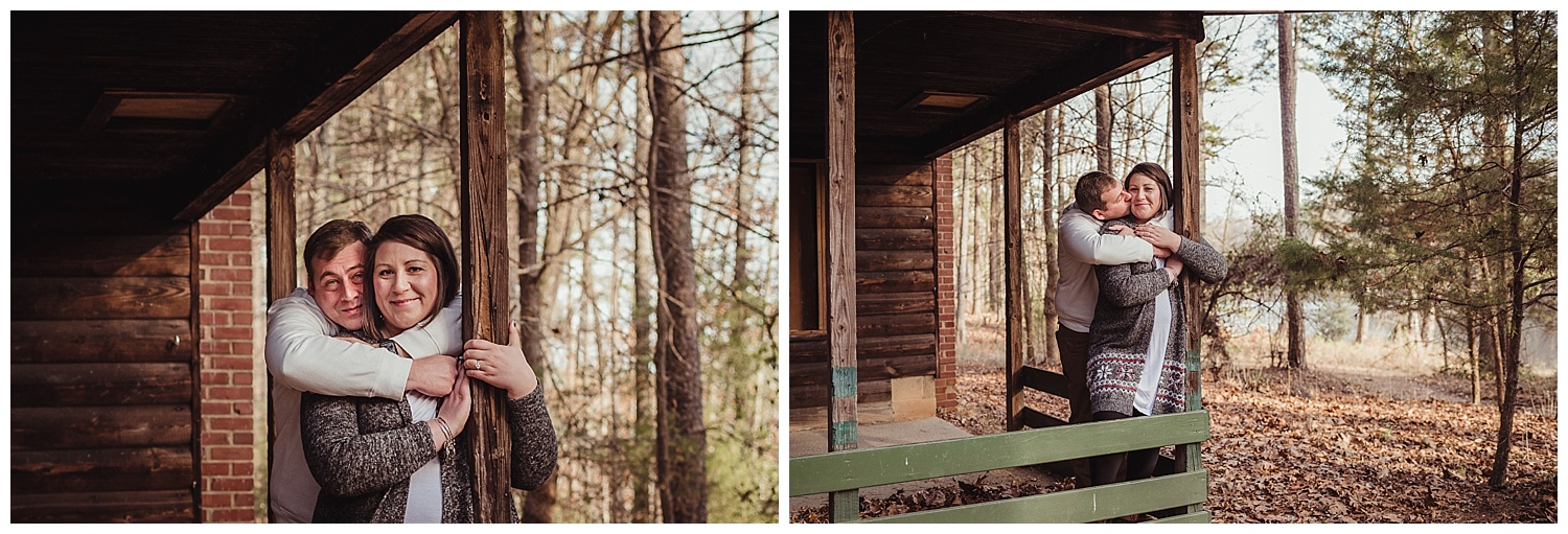 The engaged couple snuggle together by the log cabin at Durant Nature Park during their engagement pictures with Rose Trail Images.